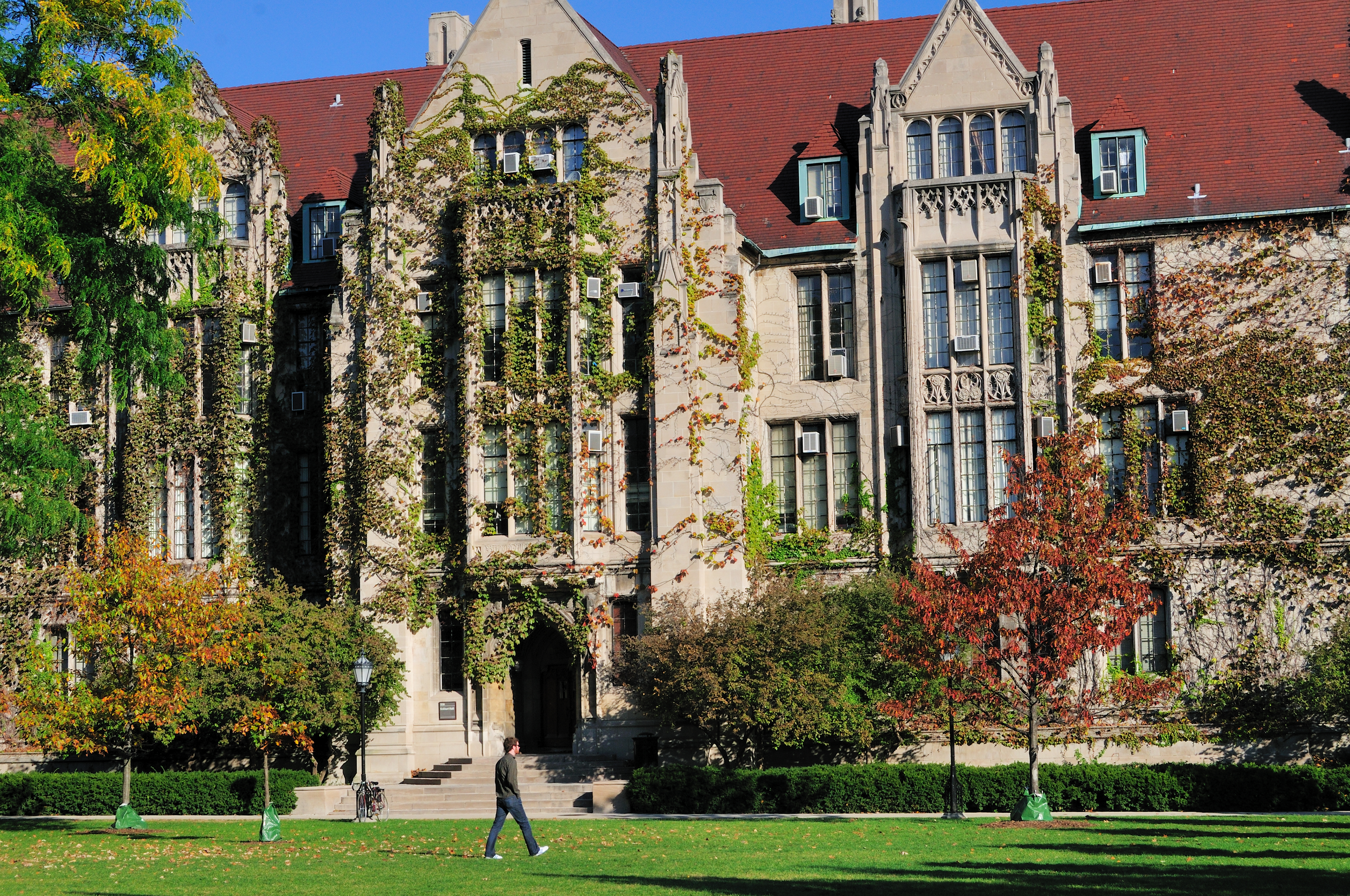 A student cust across the quadrangle in front of Eckhart Hall on the campus of the University of Chicago. Chicago, Illinois.