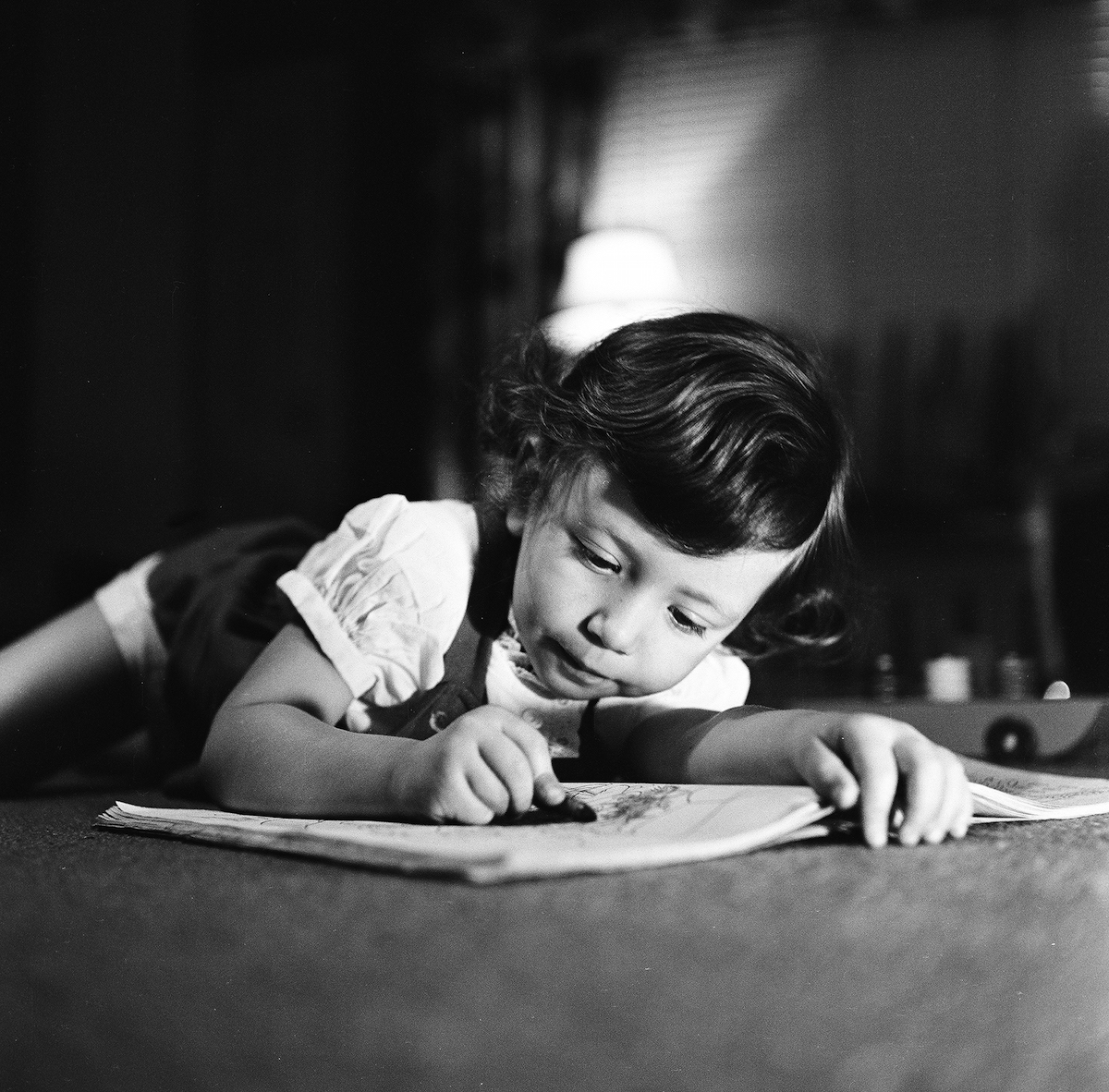 View of a young girl, filling in sketches in a coloring book, with crayon in hand, New York, 1948.