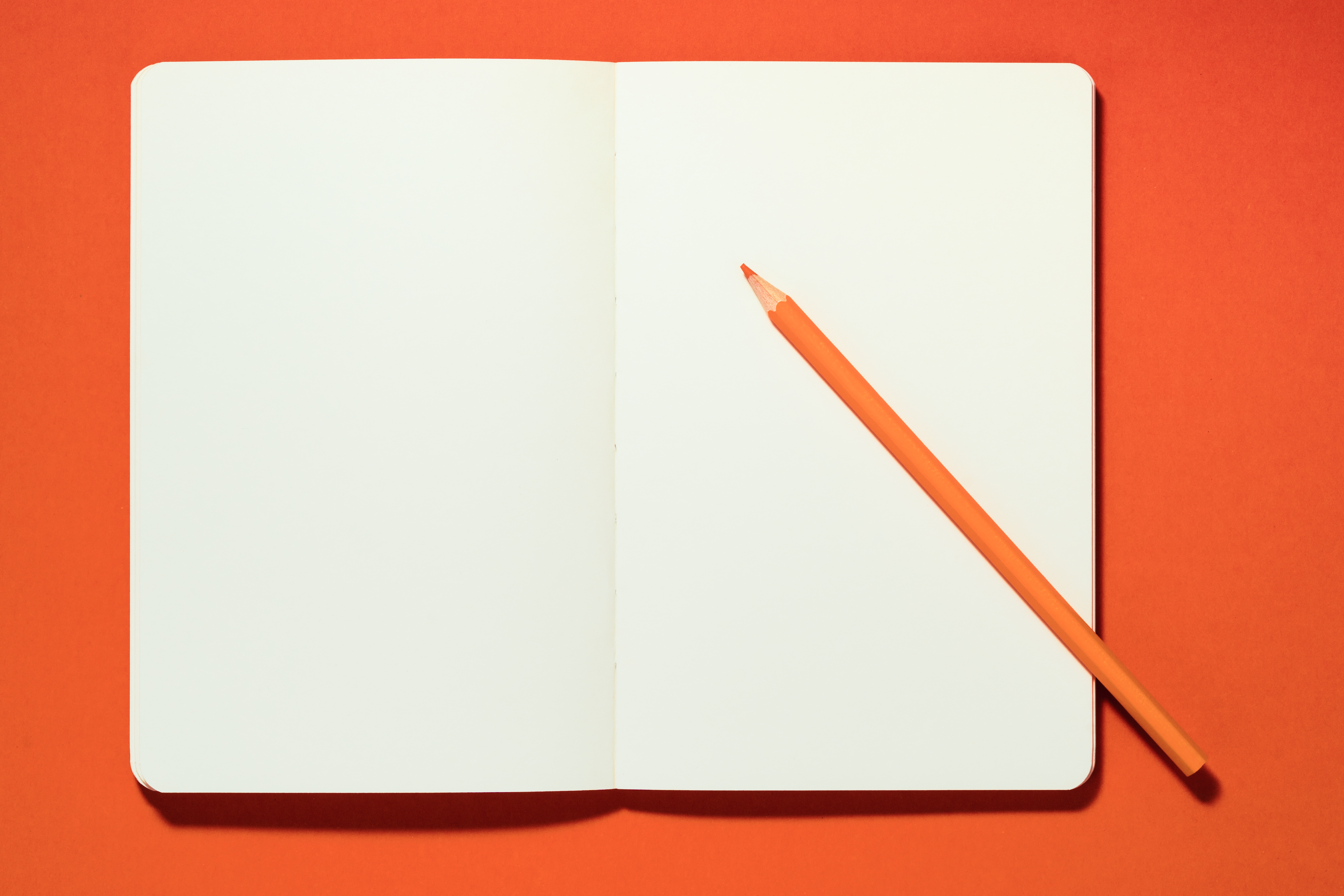 Orange Pencil on a Opened Blank Notebook against Orange Color Background Overhead View.
