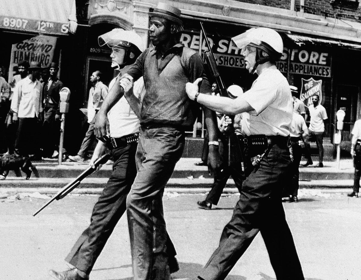 Two police officers in full riot gear arrest a man during a breakout of rioting and looting on the West side of Detroit on July 23, 1967