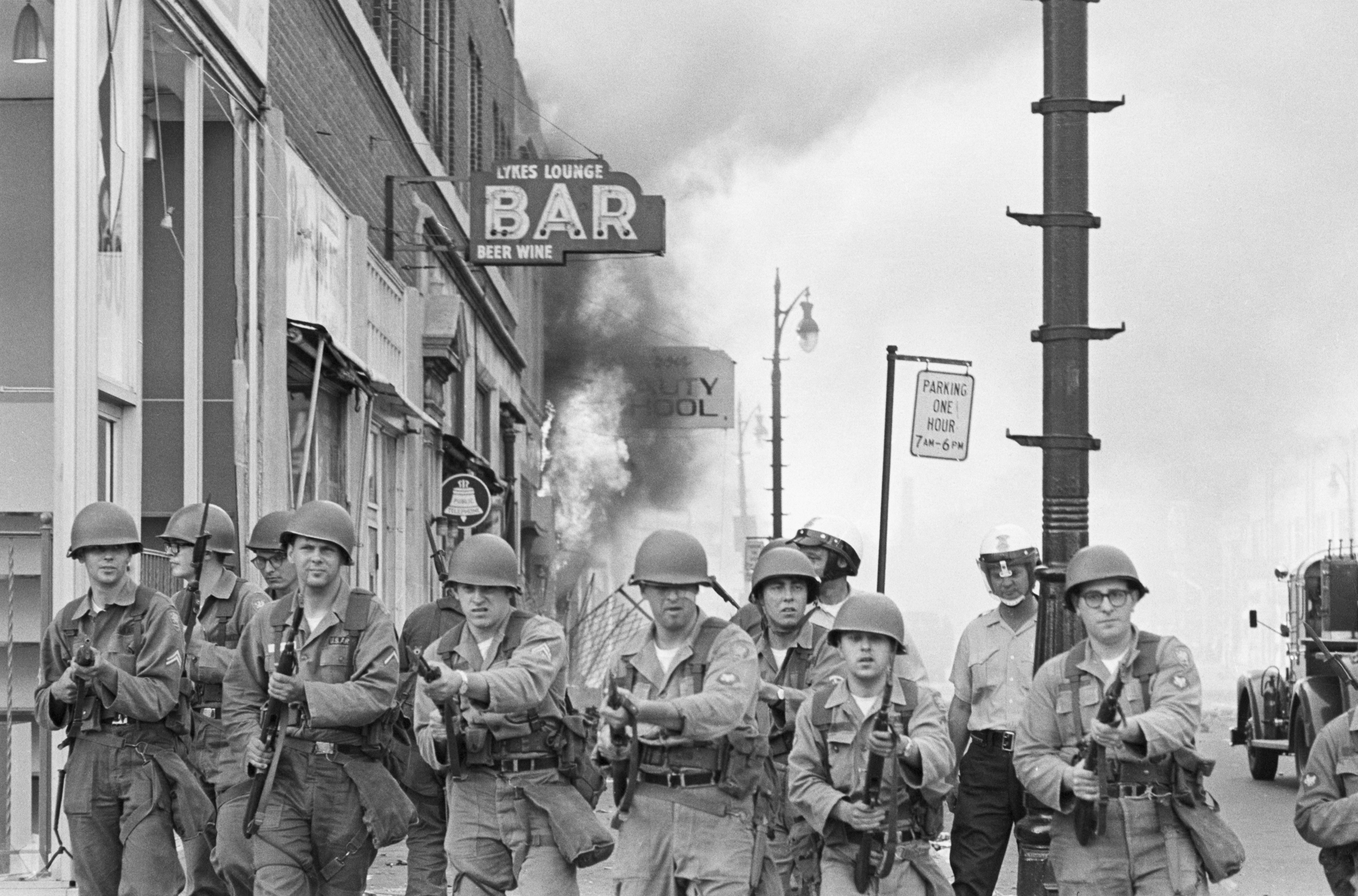 Michigan National Guardsmen push rioting citizens back from a burning Detroit building with fixed bayonets in July of 1967.