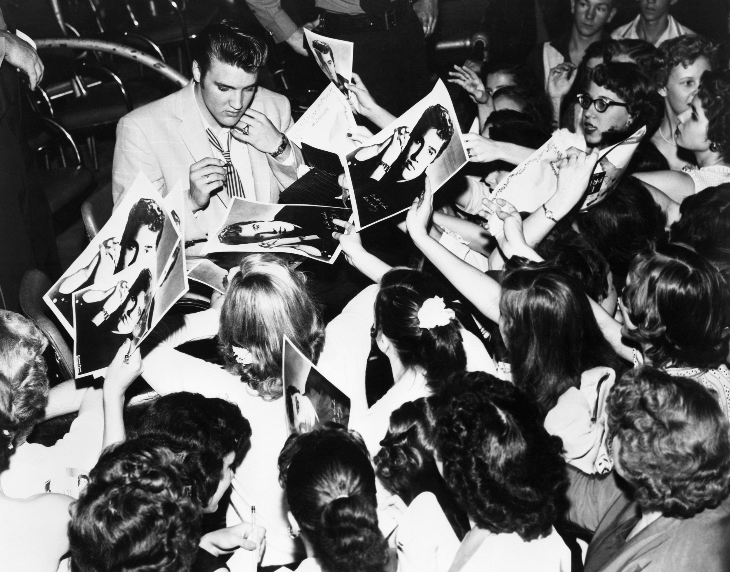 Elvis is surrounded by his enthusiastic teenage fans in Houston, TX., 1956.