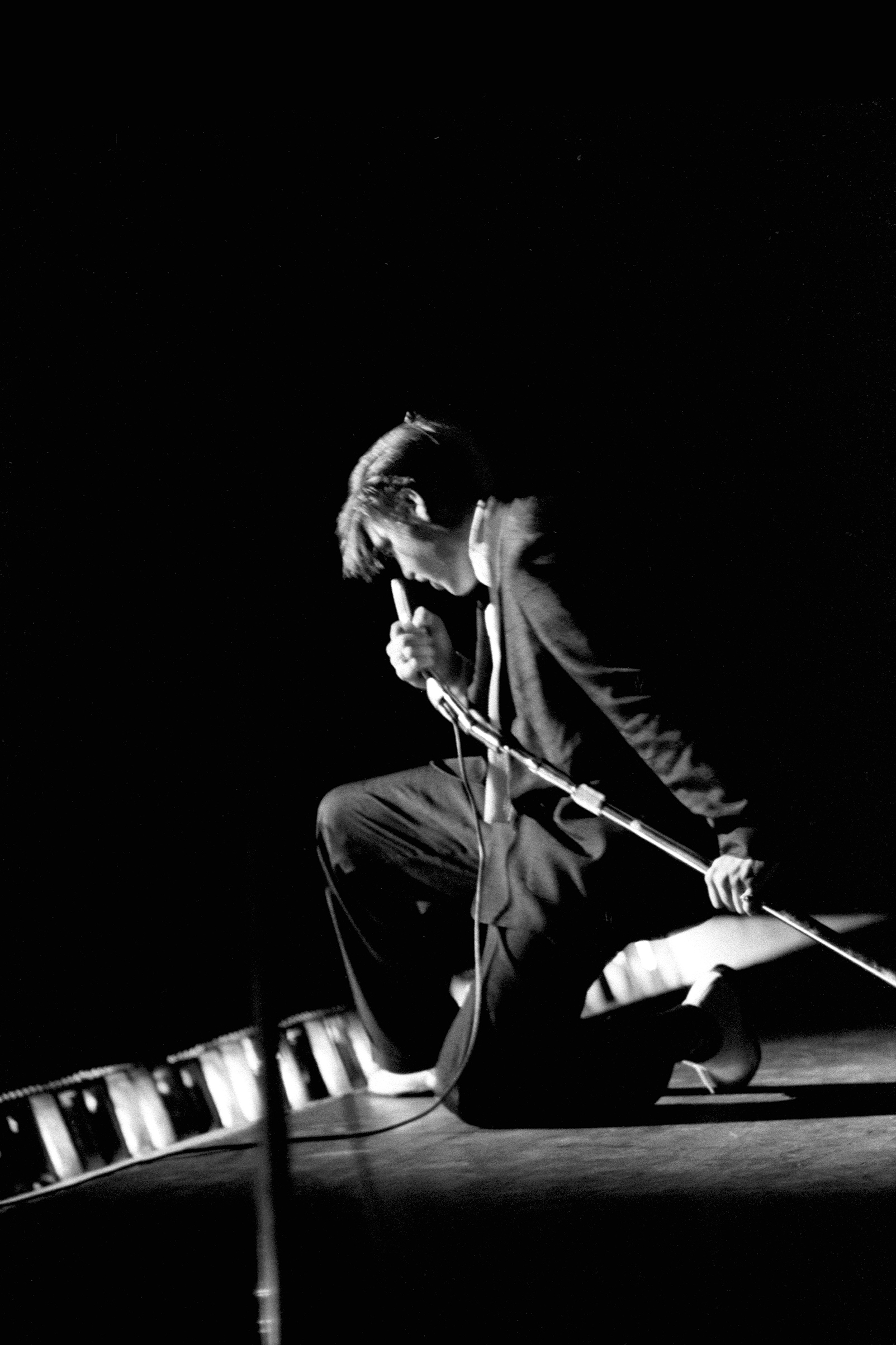 Elvis kneels onstage as he performs at the Mosque Theater, Richmond, Va., June 30, 1956.