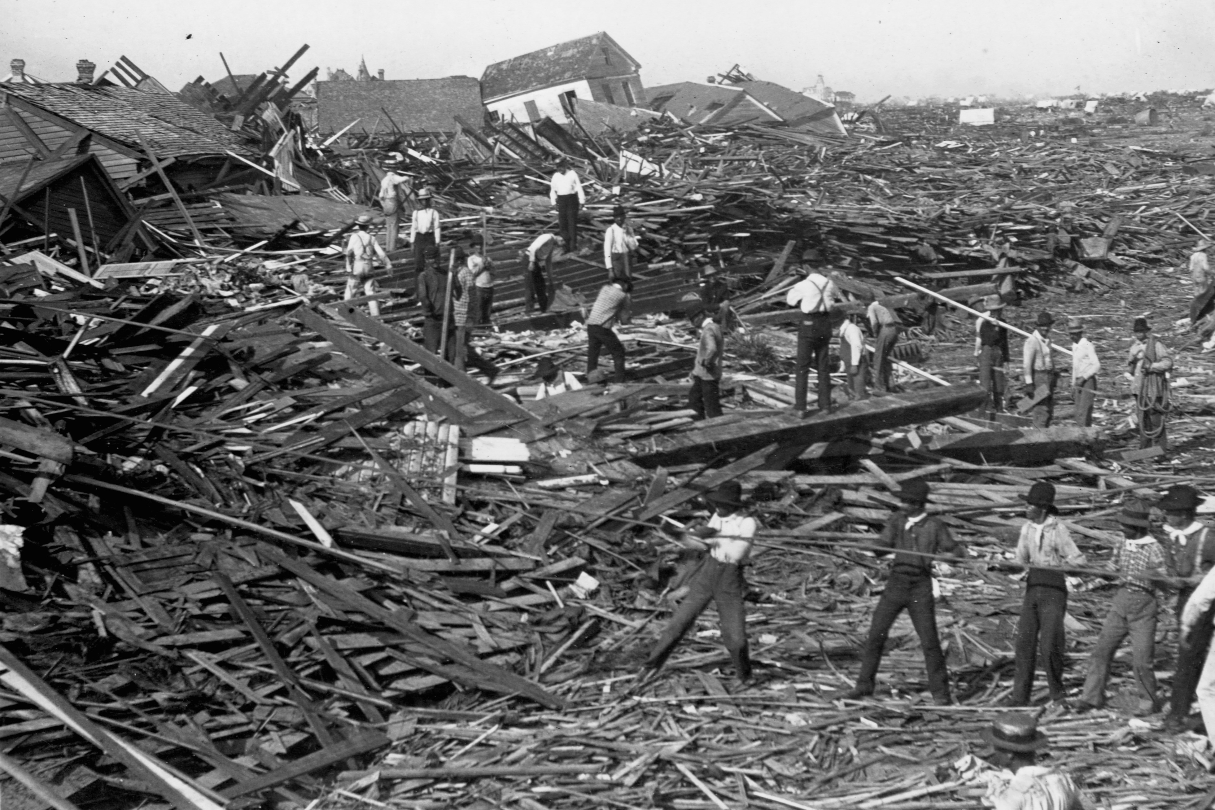 Men use ropes to pull away the debris of houses in order to look for bodies, after the Galveston Hurricane of 1900.