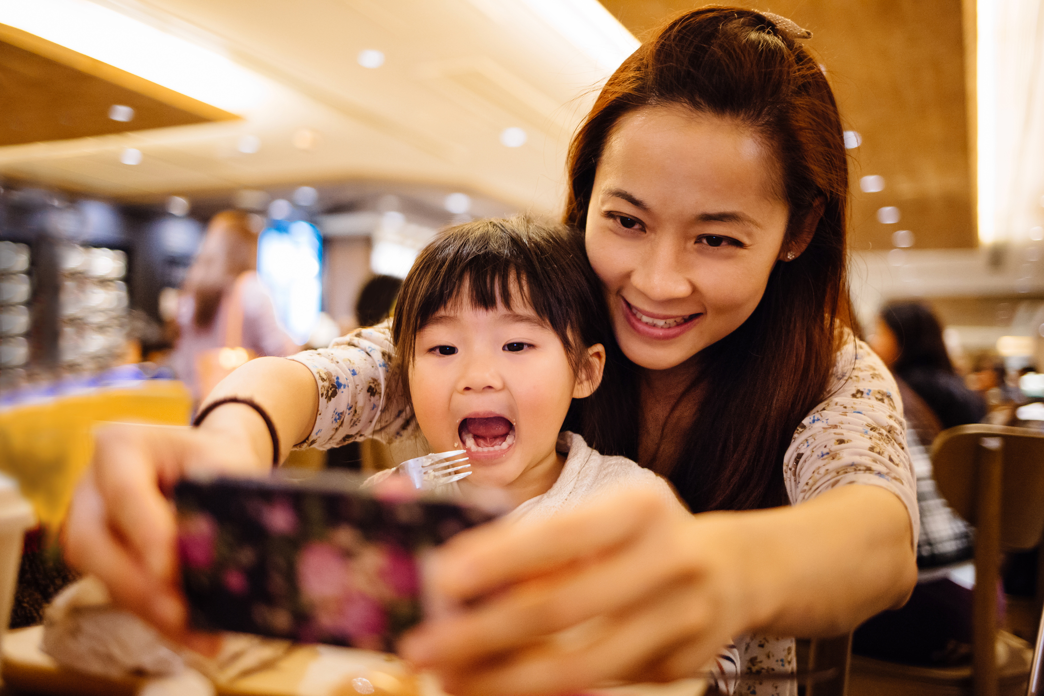 Lovely toddler girl sitting in mom's lap taking self portraits joyfully with mom using the smartphone in the cafe
