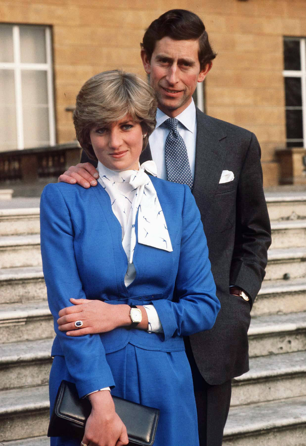 Diana selected a deep blue skirt suit and white pussy bow blouse for her official engagement photos in 1981; the suit's color complemented the sapphire engagement ring she received from Prince Charles.