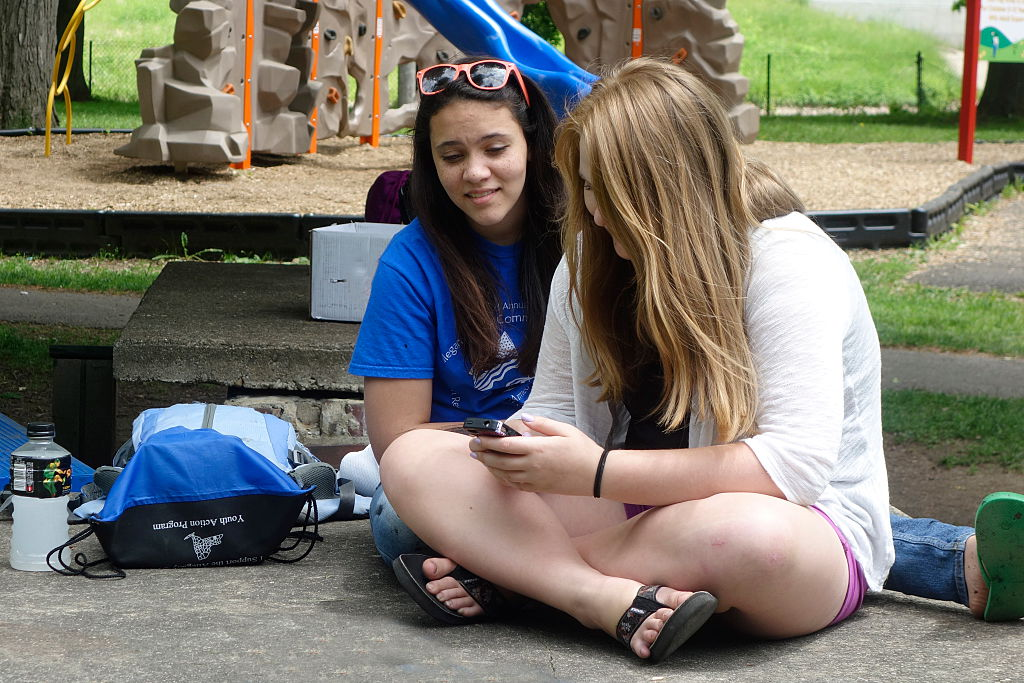 Teenage Girls Checking Smartphone, Wellsville, New York, United States . (Photo By: Education Images/UIG via Getty Images)