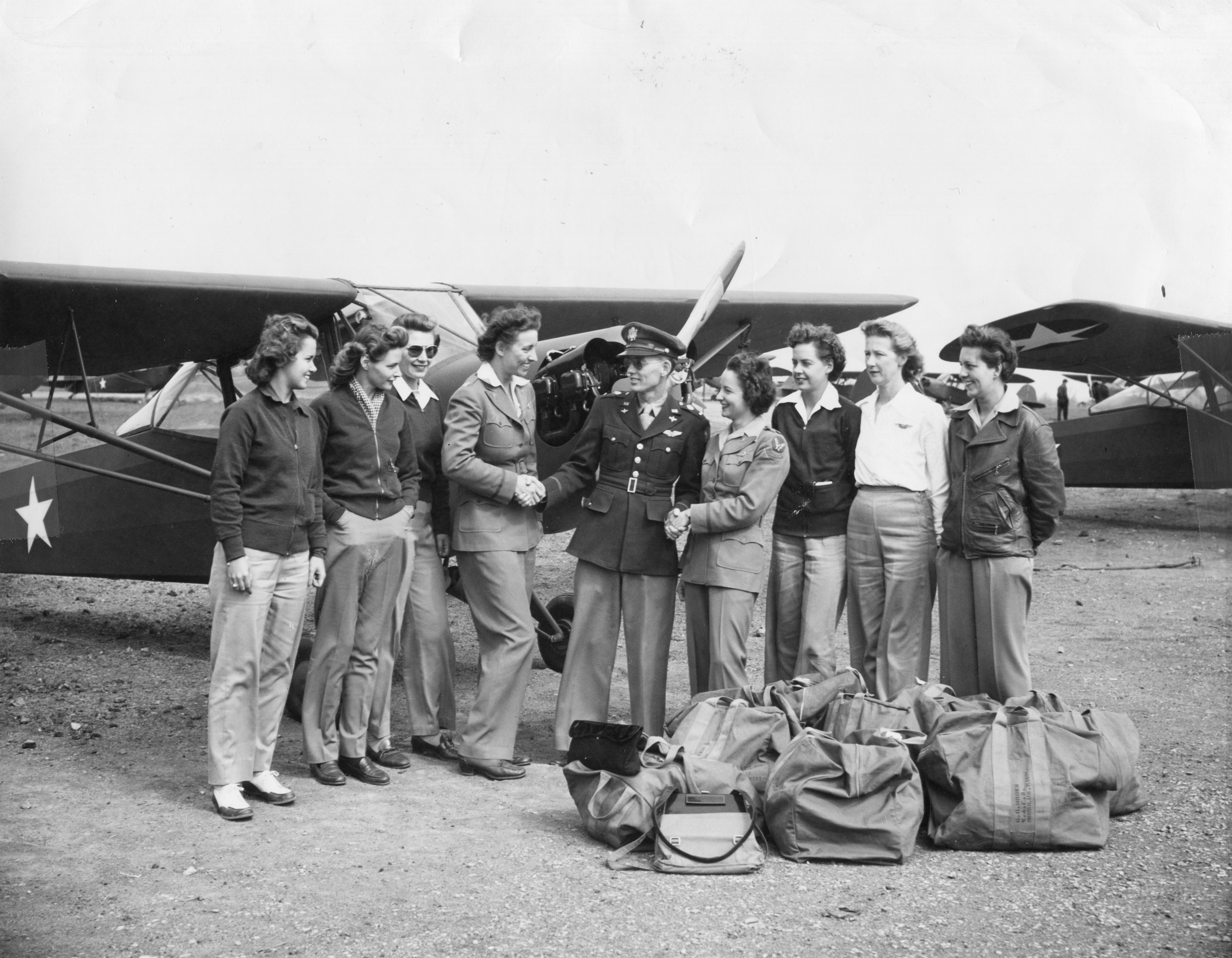 American military commander Lt. George Fairfield (center) shakes hands with Women's Air Force Service Pilot (WASP), and former Olympic swimming champion, Katherine Rawls Thompson (fourth left), and another unidentified pilot, as they are watched by six additional WASPs, all of whom had flown L-2 'Grasshopper' liaison planes to various Army bases from the Taylorcraft factory, Alliance, Ohio, in June 1943.
