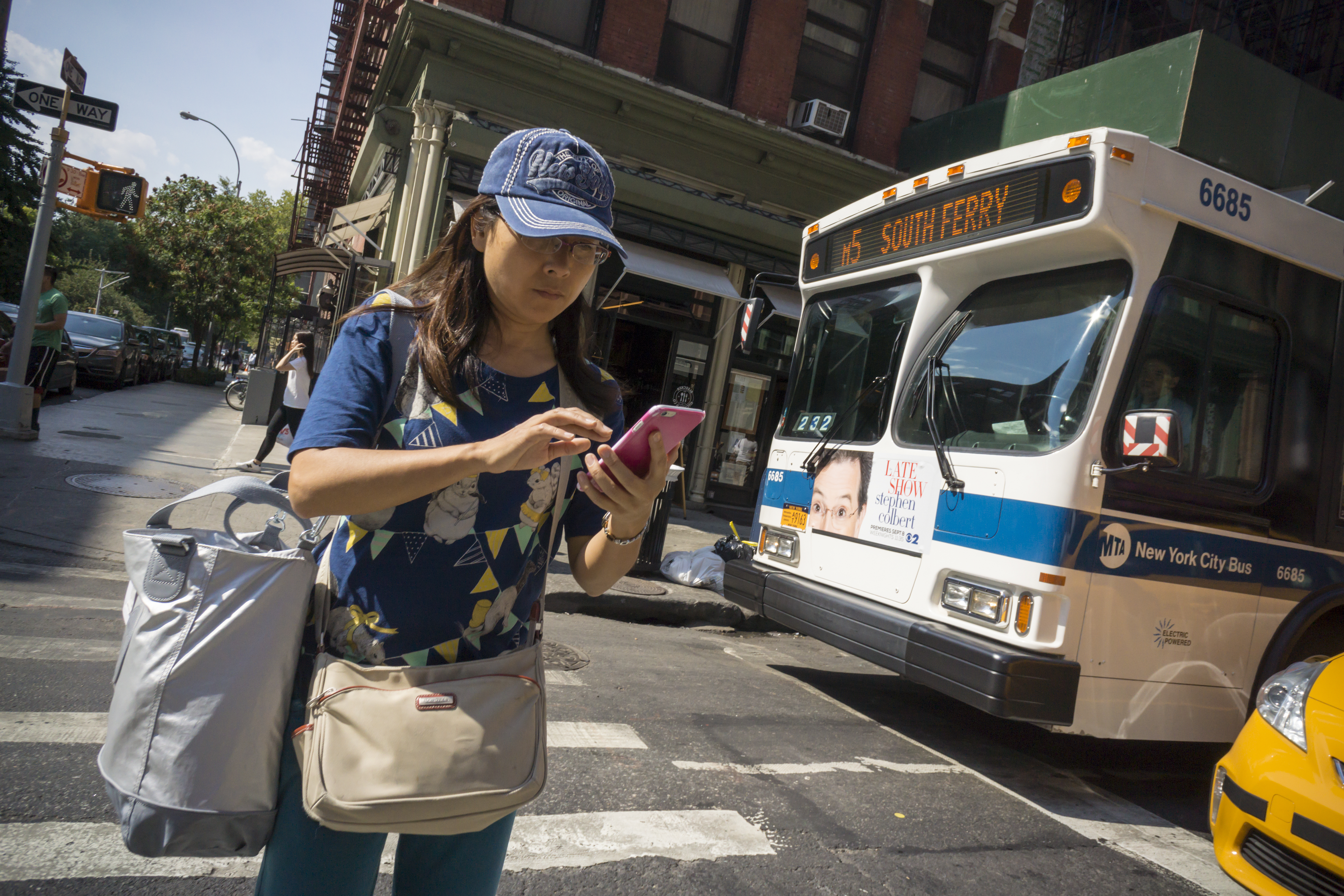 A pedestrian checks her smartphone on Broadway in New York on Saturday, August 28, 2015. A bill introduced in New Jersey would make it illegal for anyone to text and walk at the same time. Offenders could be fined $50 and/or 15 days in jail. No date has been set for when this bill will be voted on. (© Richard B. Levine) (Photo by Richard Levine/Corbis via Getty Images)