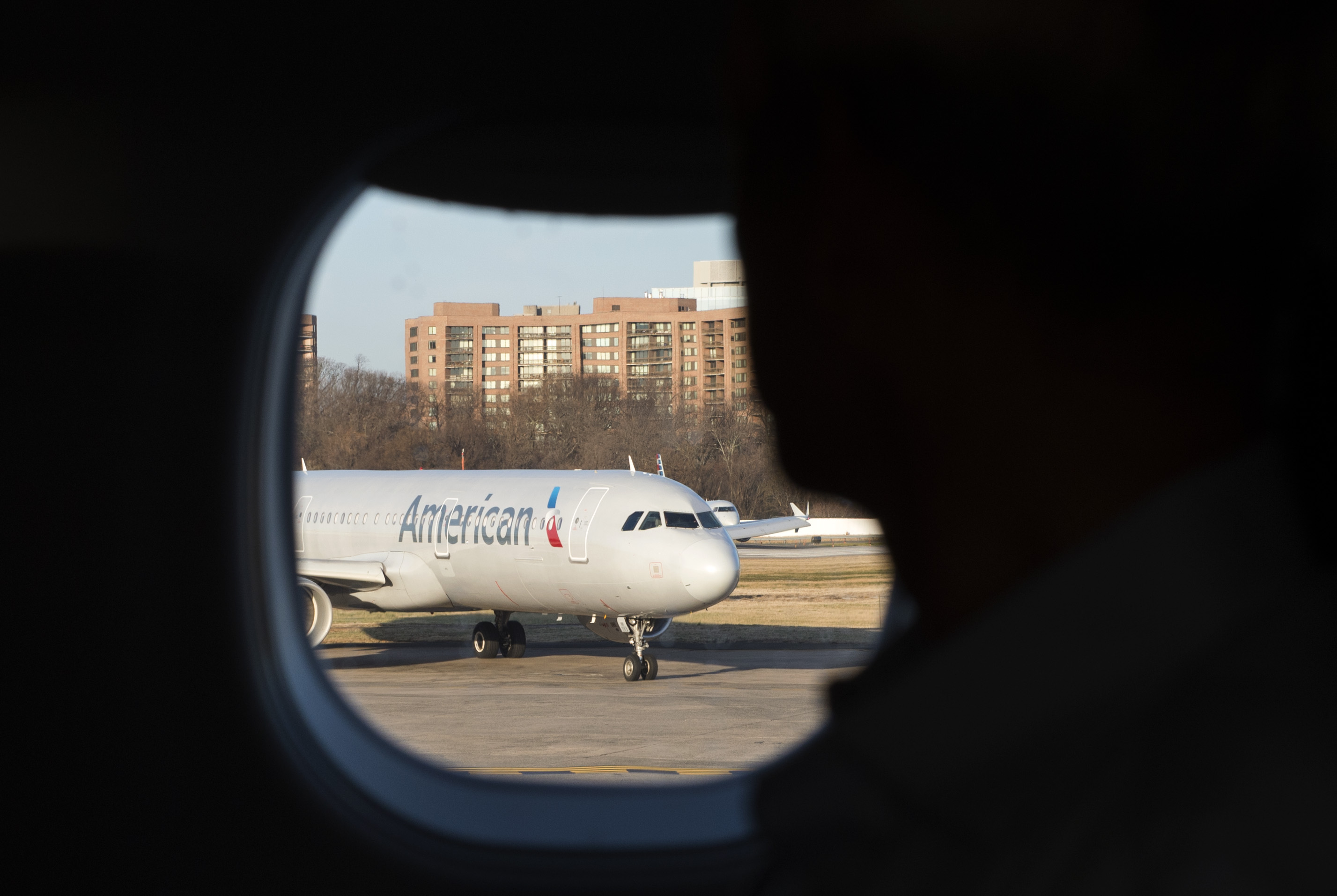 A man looks out his window at an American Airlines plane at Reagan National Airport in Arlington, Virginia on February 24, 2017.
