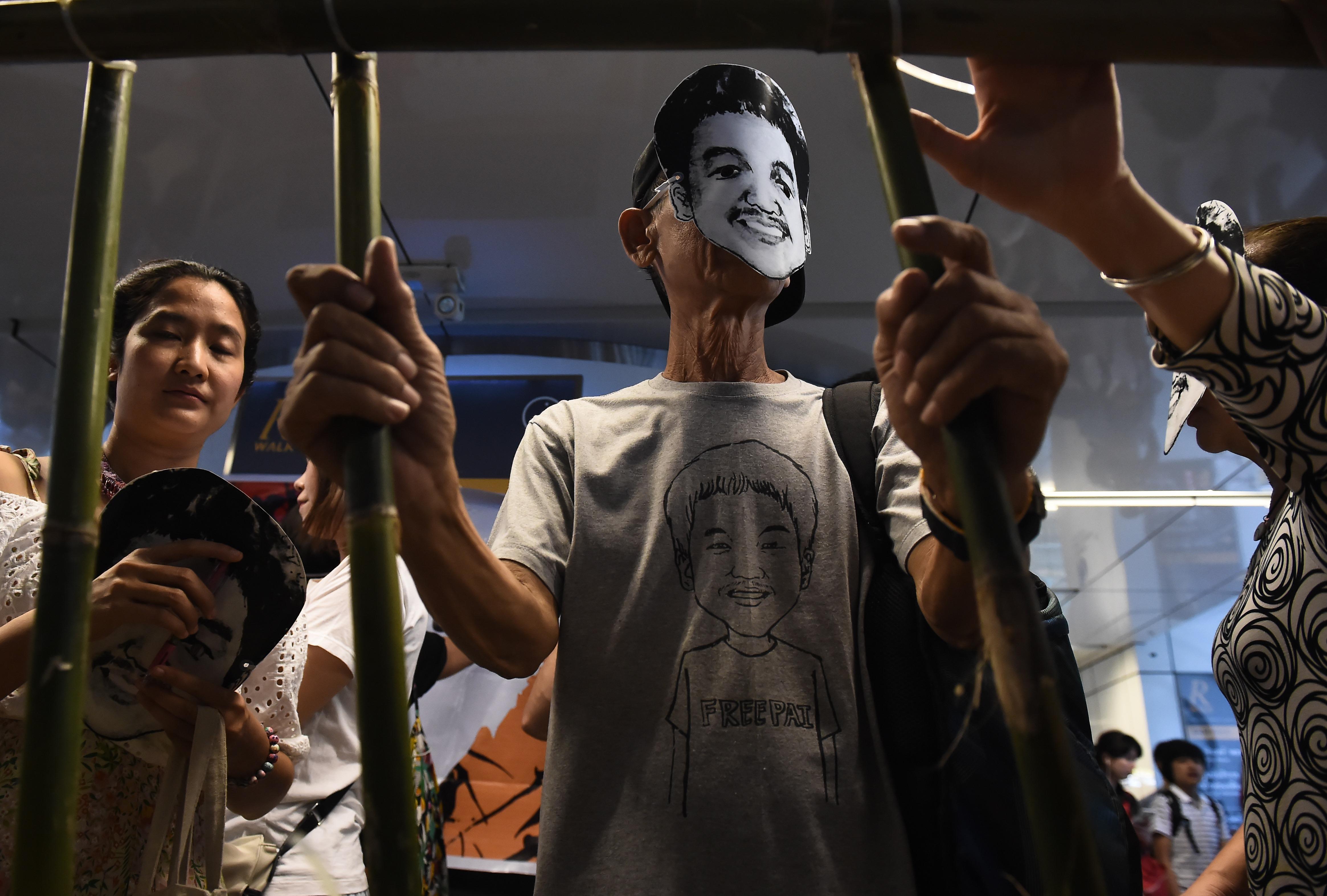 People stand behind makeshift bars wearing masks of Thai human rights activist Jatupat Pai Boonpattararaksa in Bangkok on June 22, 2017.