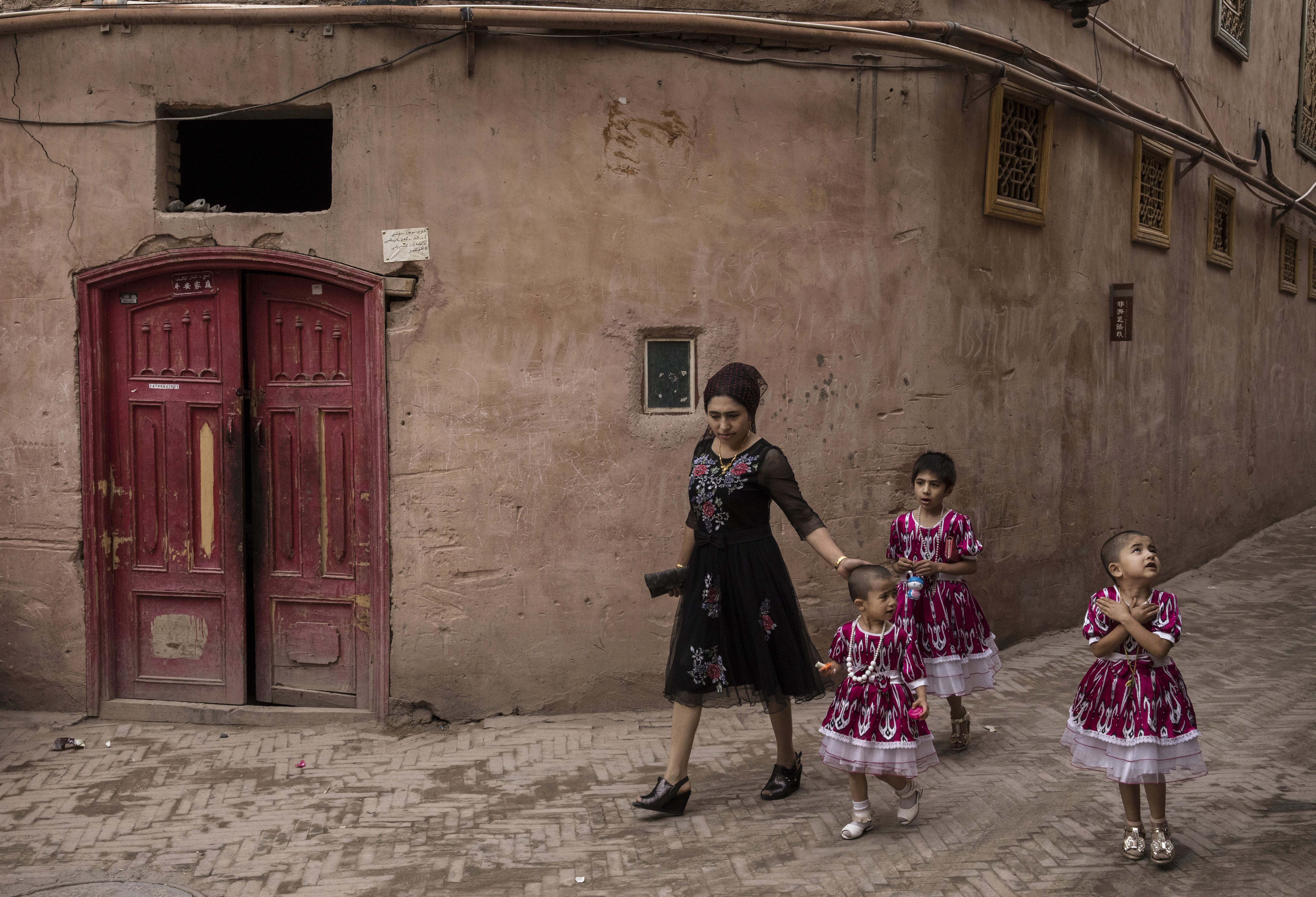 An ethnic Uighur woman walks with her children in Kashgar, Xinjiang, on June 28, 2017.