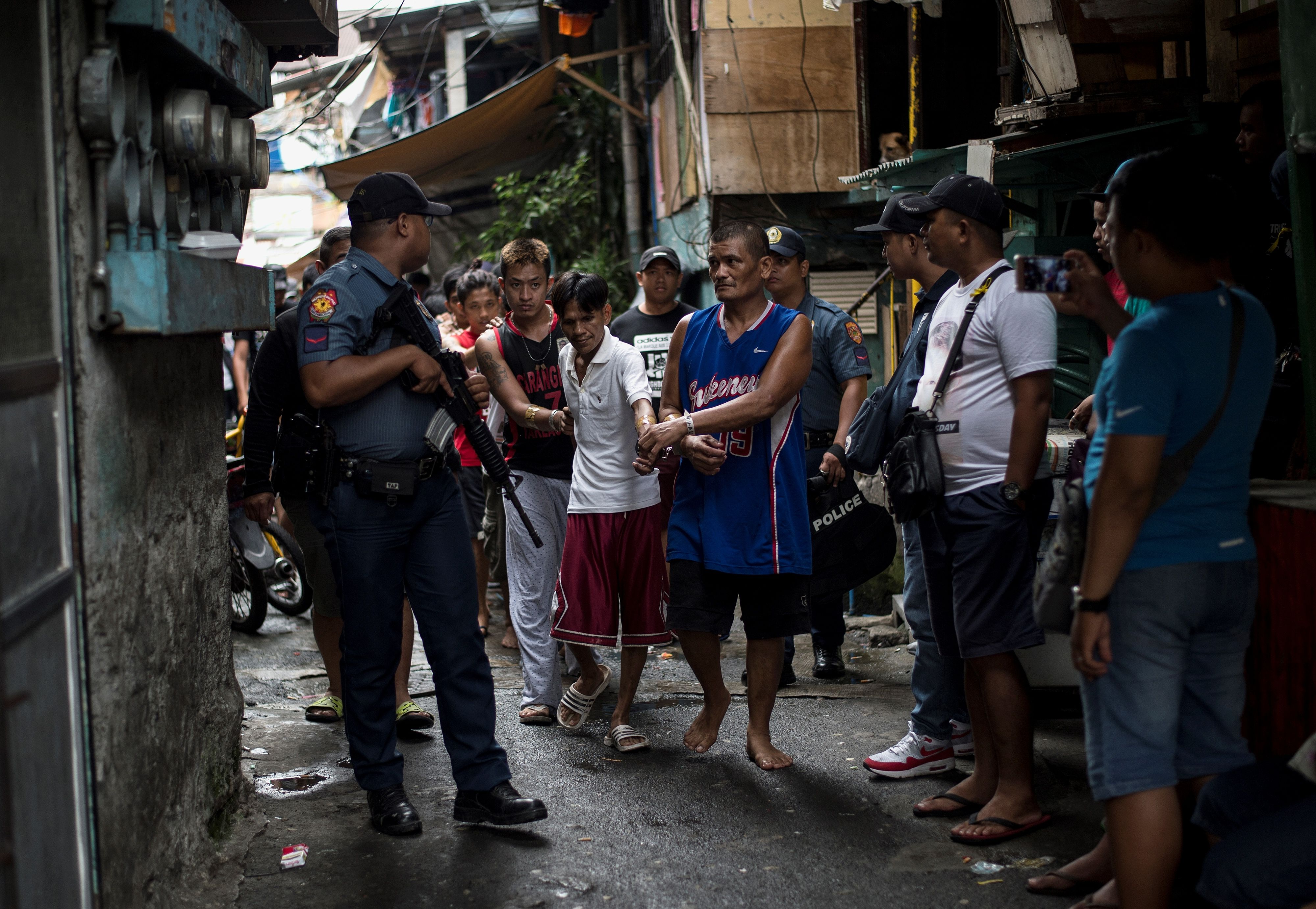 Male residents are rounded up for verification after police officers conducted a large scale anti-drug raid at a slum community in Manila on July 20, 2017.