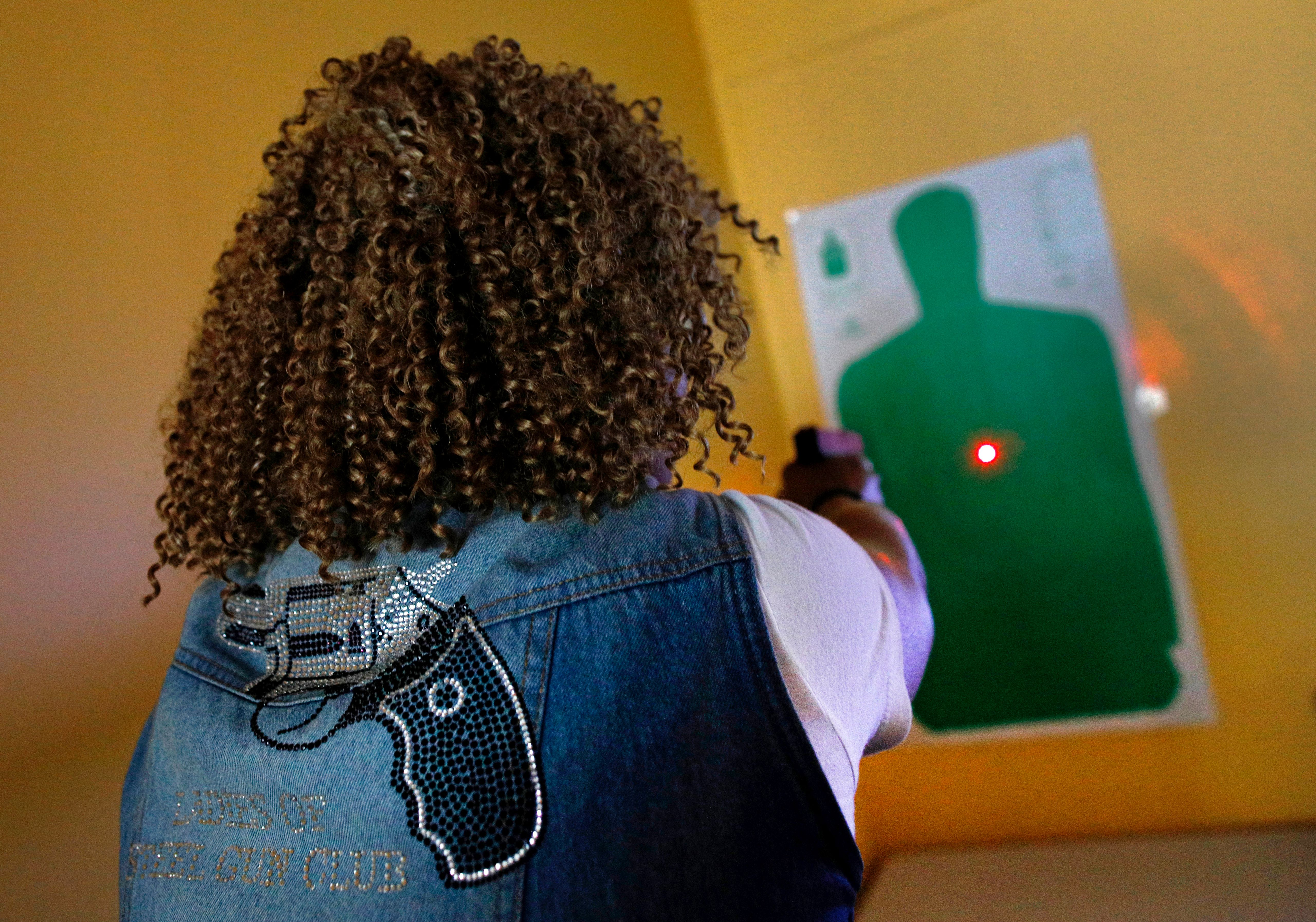Javondlynn Dunagan of JMD Defense and Investigations demonstrates the laser on a Shot Indicating Resetting Trigger (SIRT) Training Pistol in her training classroom in Chicago, Illinois, July 19, 2017.