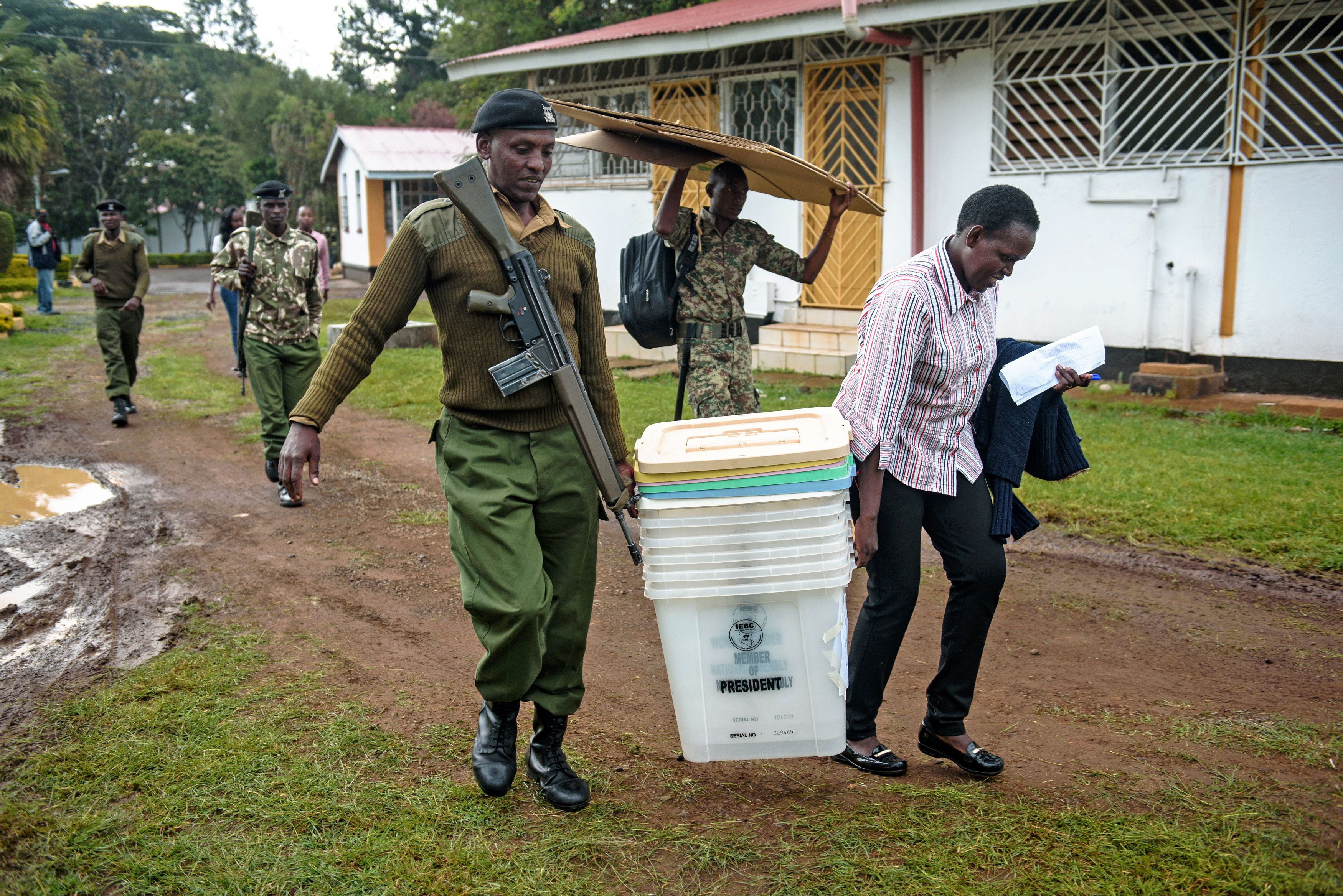 A police officer and an polling official carry ballot boxes in Eldoret, Kenya on Aug. 7, 2017.