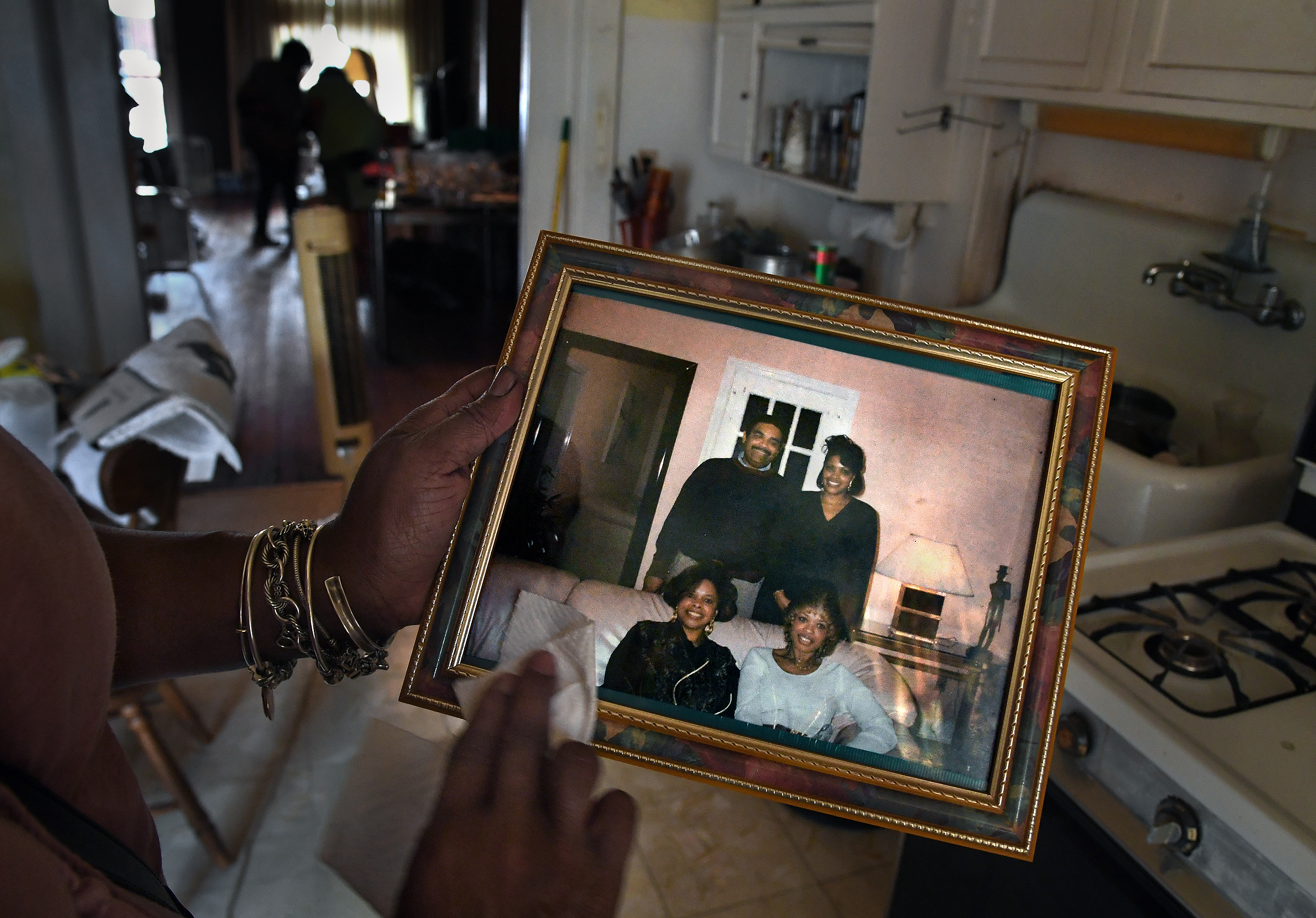 Kimberly Ware cleans a family photo she found at the house of her deceased grandfather, Wadell Tate, in Baltimore on July 27, 2017.