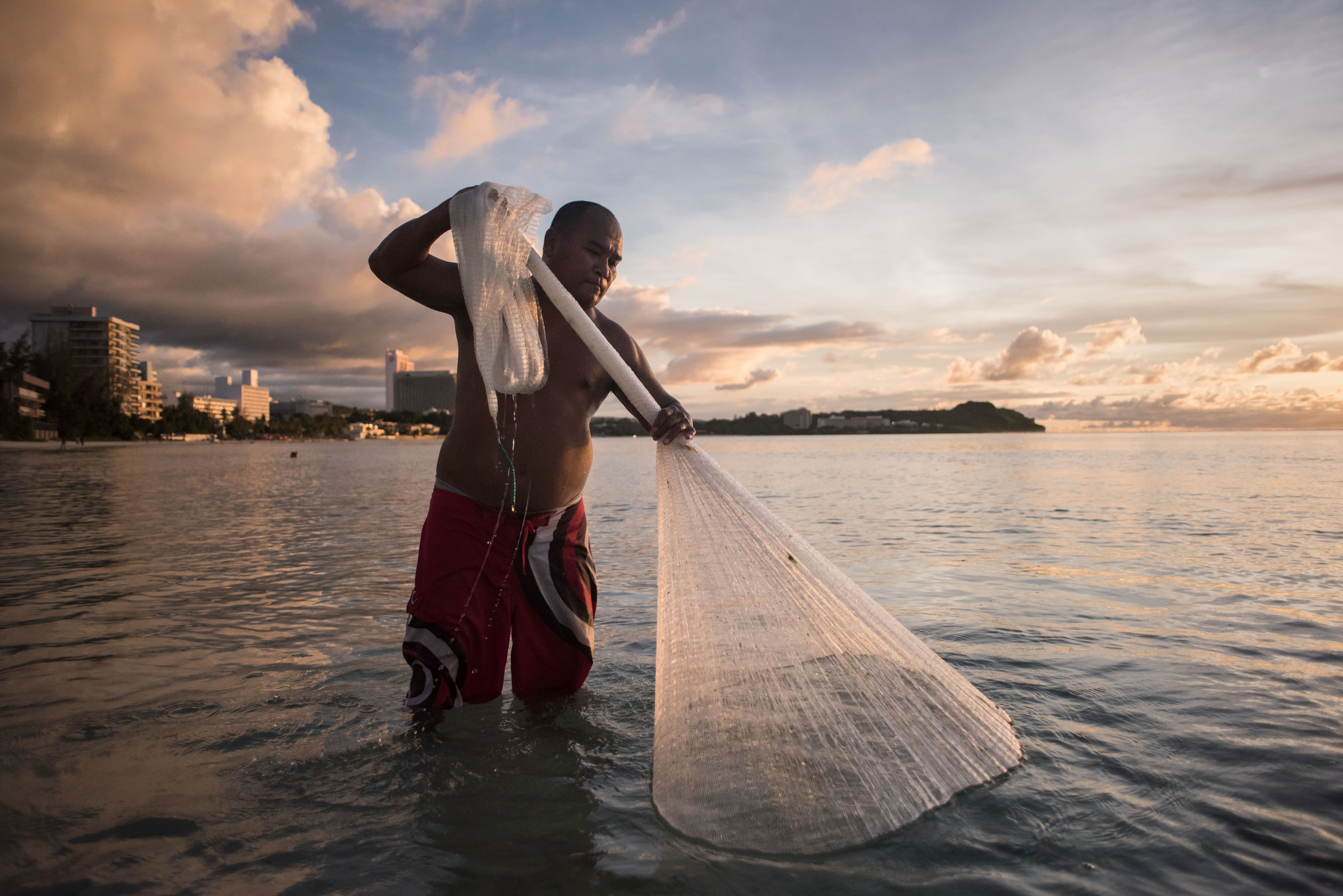 This photograph taken on August 12, 2017, shows a fisherman catching 'goat fish' off a beach at Tumon Bay in Guam.