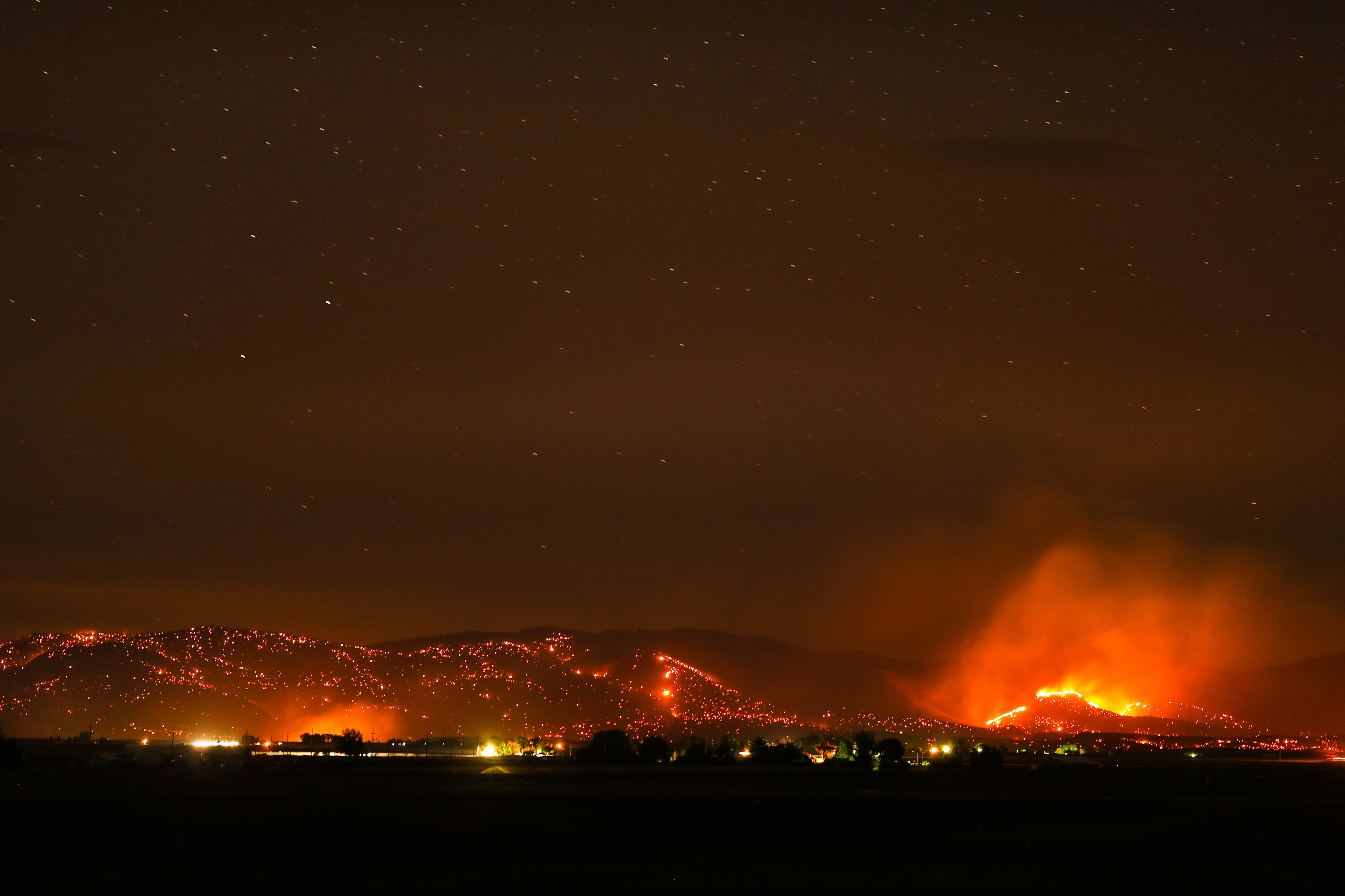 A wildfire burns in sagebrush and grass on a sidehill in Warm Springs, Oregon on August 18, 2017. The fire is burning over 60,000 acres and is displacing visitors hoping to have clear skies for the total solar eclipse Monday. Total solar eclipse enthusiasts gather in Madras, Oregon on August 18, 2017.