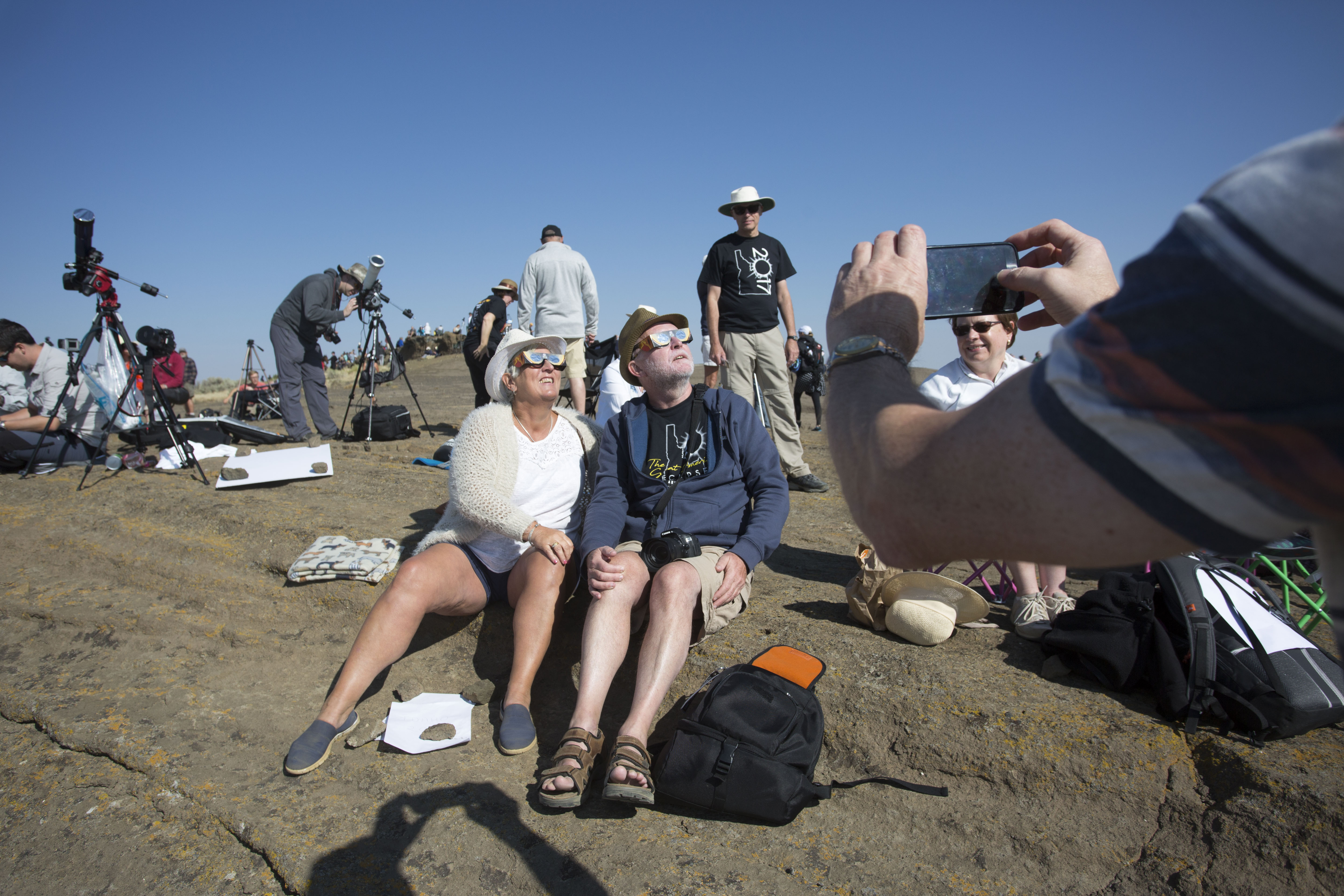 MENAN, ID - AUGUST 21: Angela and Chris Willis-Richards of London get their photo taken as they wear eclipse glasses on Menan Butte to watch the eclipse on August 21, 2017 in Menan, Idaho. Millions of people have flocked to areas of the U.S. that are in the  path of totality  in order to experience a total solar eclipse. (Photo by Natalie Behring/Getty Images)