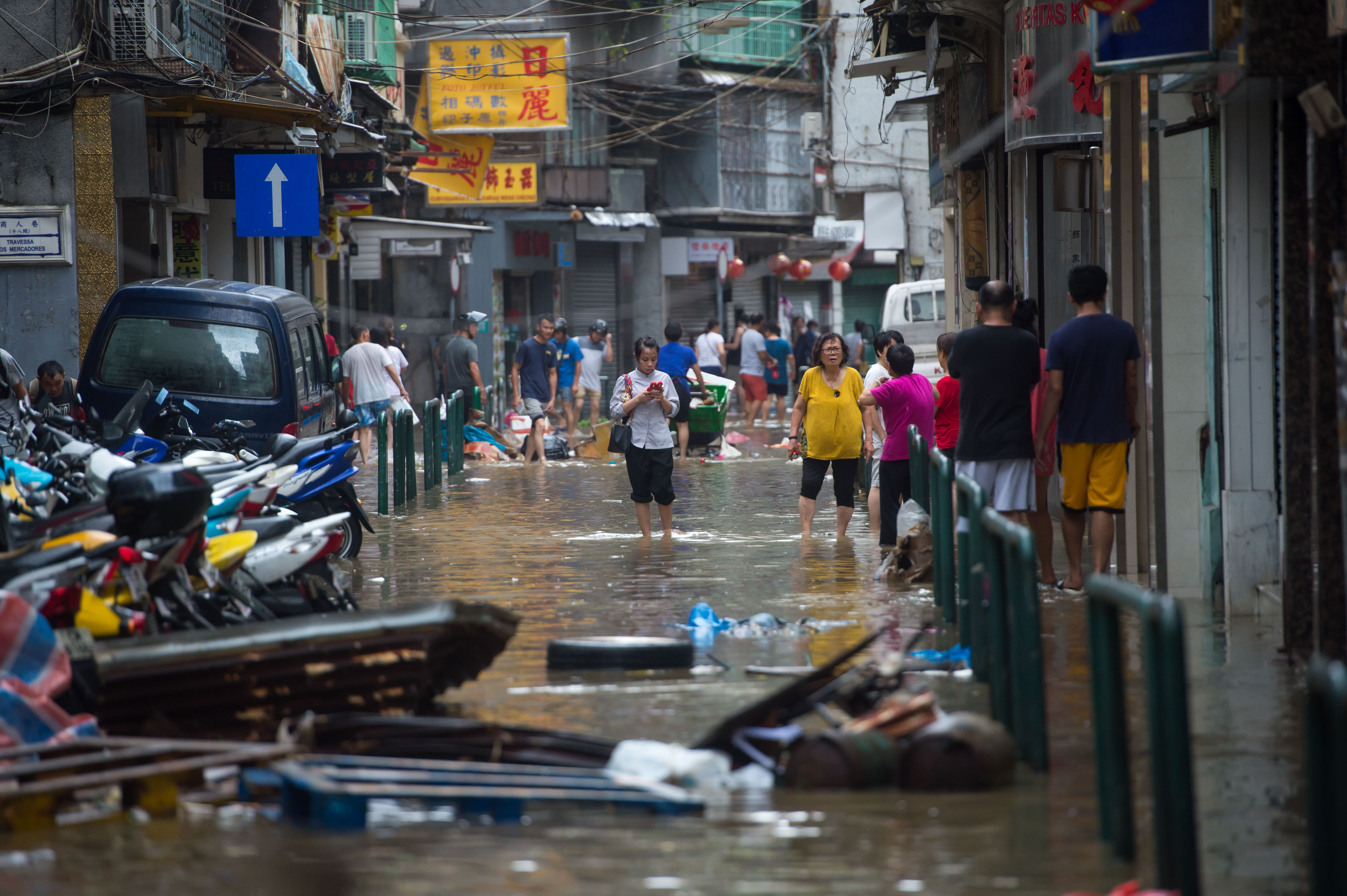 Residents wade through a water-logged street in Macau, Aug. 23, 2017.