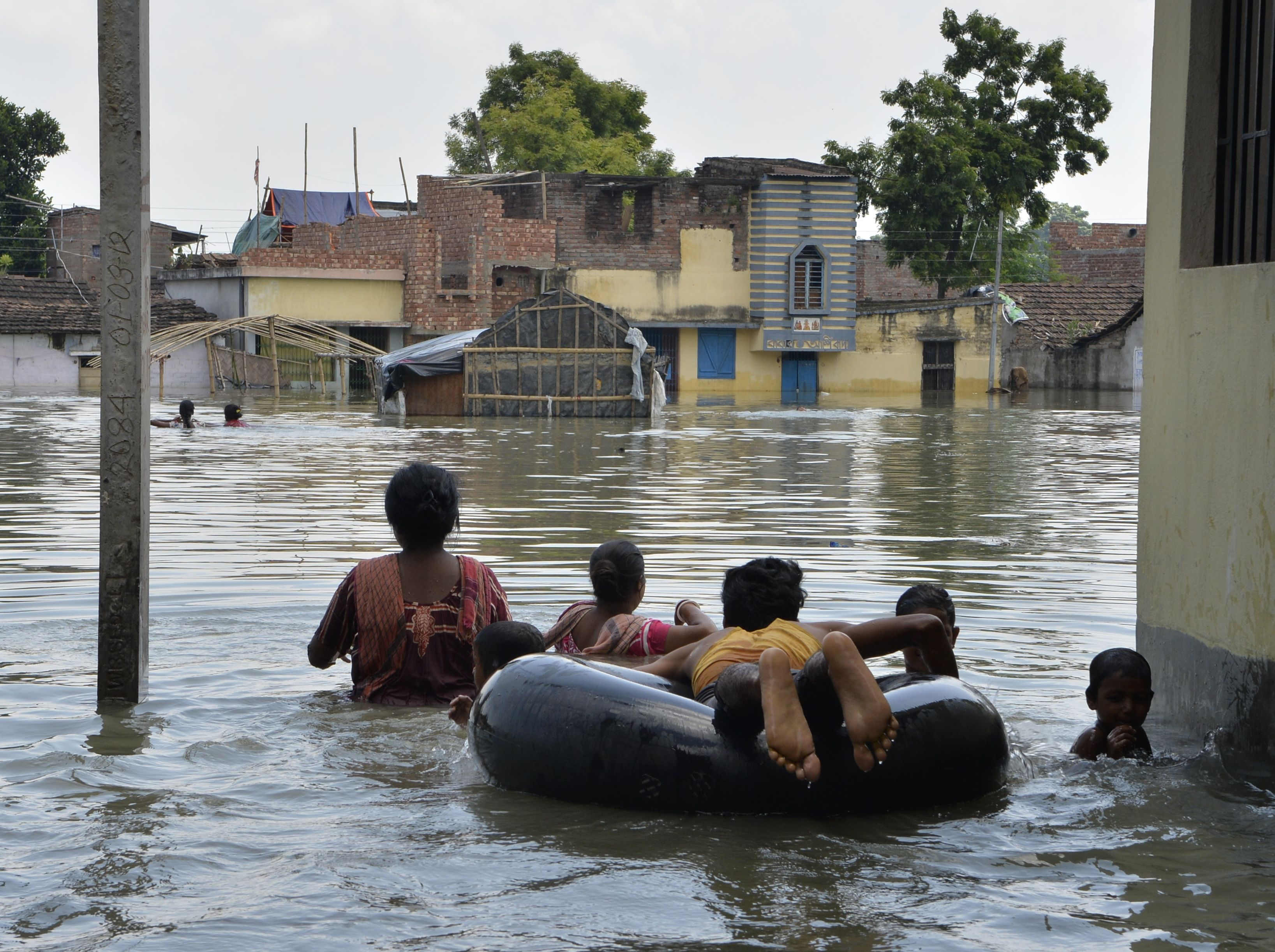 Indian residents wade through flood waters in the Indian state of West Bengal on Aug. 24, 2017.