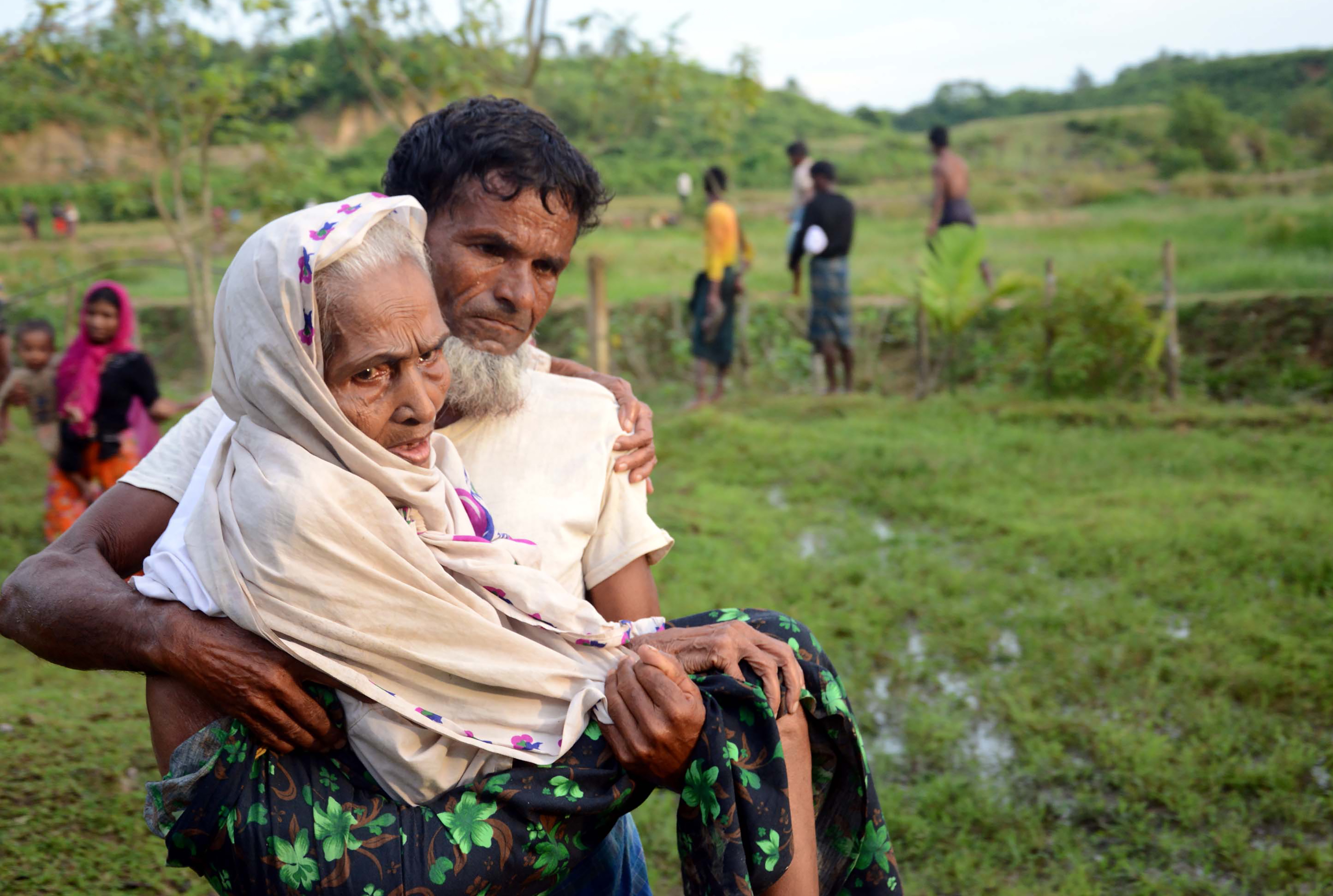 This Aug. 30, 2017 photo shows a Rohingya man carrying his mother in Ukhiya after crossing the Bangladesh-Myanmar border.