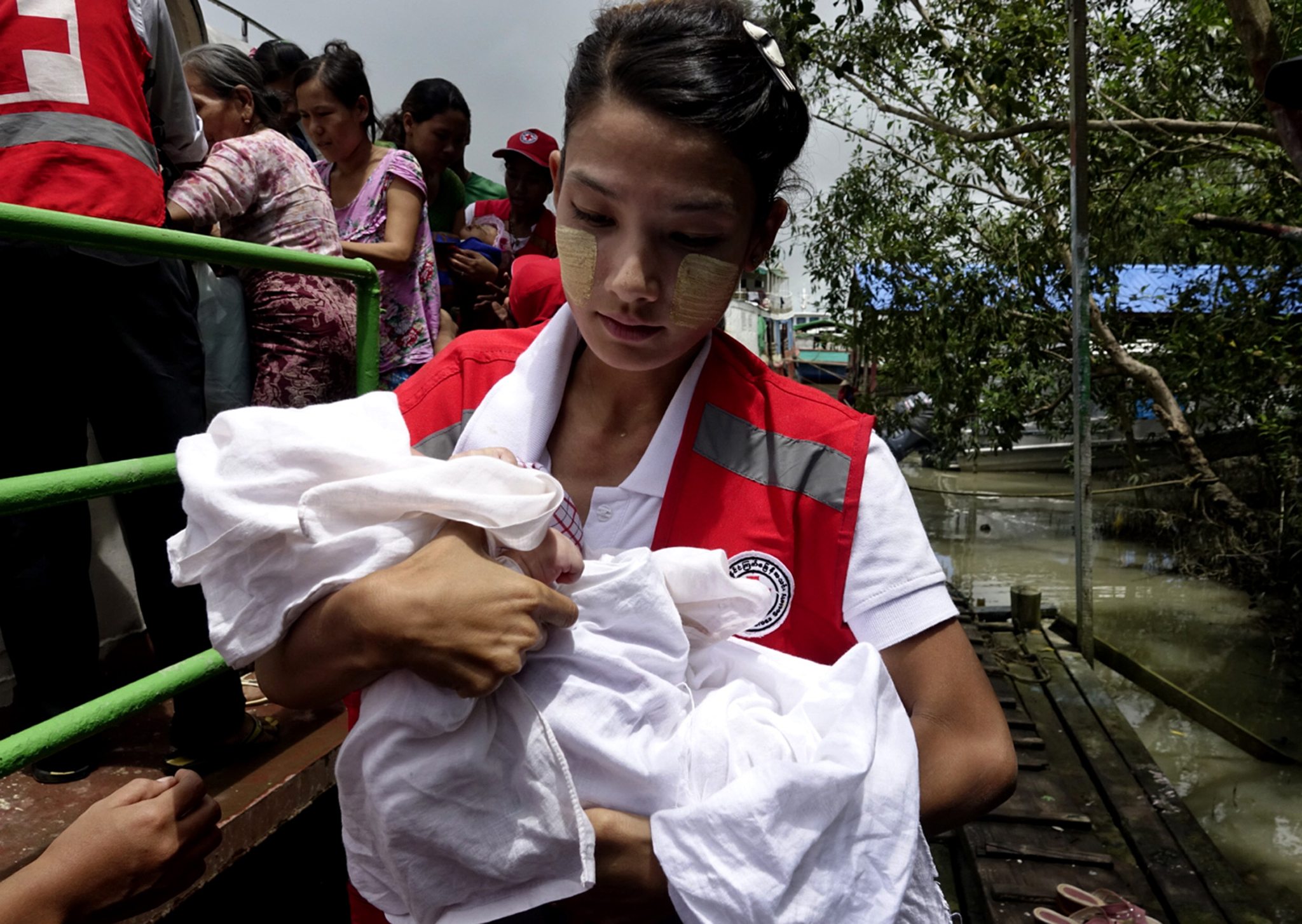 A Red Cross volunteer carries a child who was displaced together with a Rakhine ethnic woman from Maungdaw at the Sittwe port, Rakhine State, Myanmar, 30 Aug. 2017.
