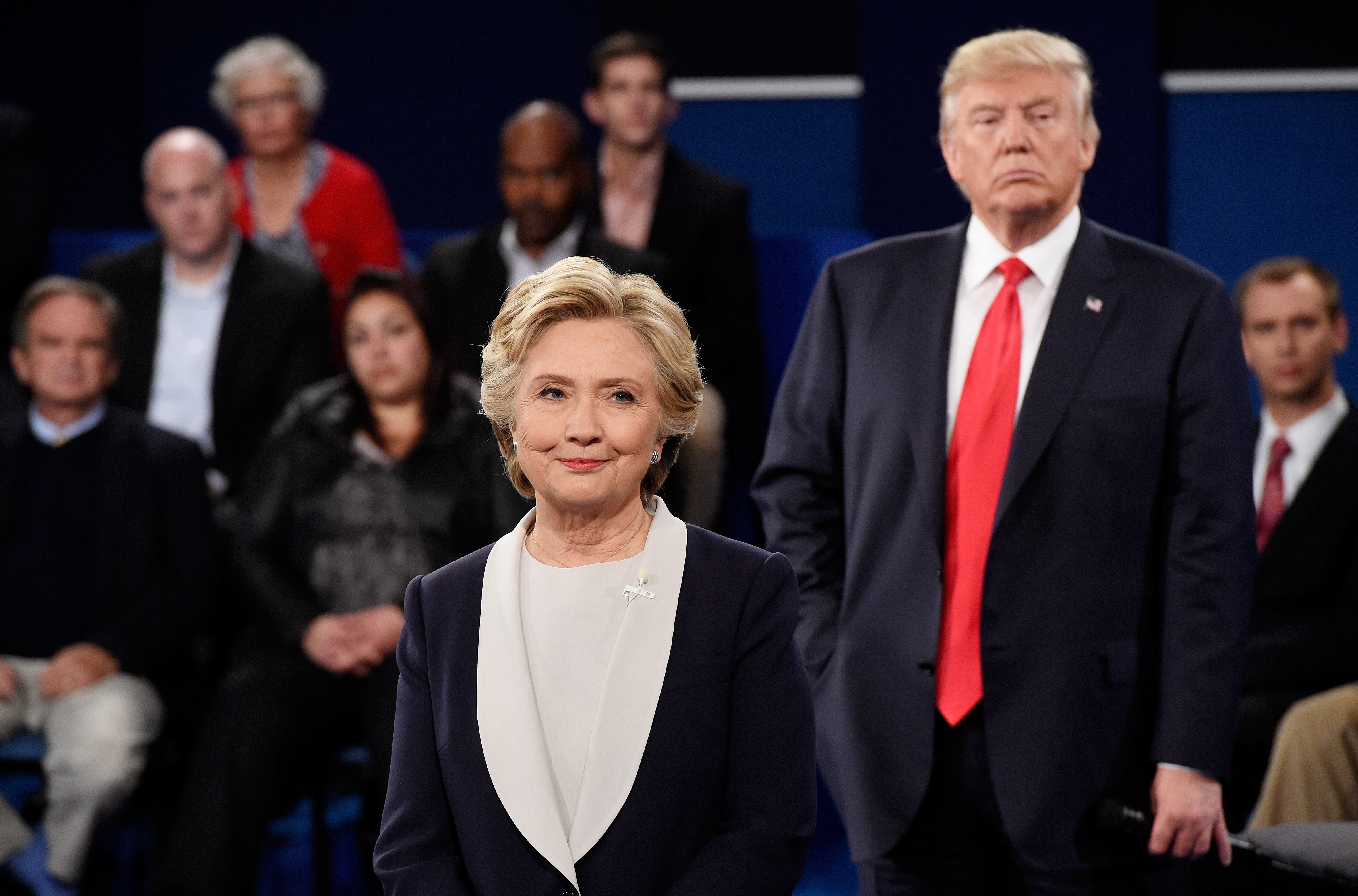 Democratic presidential nominee former Secretary of State Hillary Clinton (L) and then-Republican presidential nominee Donald Trump listen during the town hall debate at Washington University on Oct 9, 2016 in St Louis, Missouri.