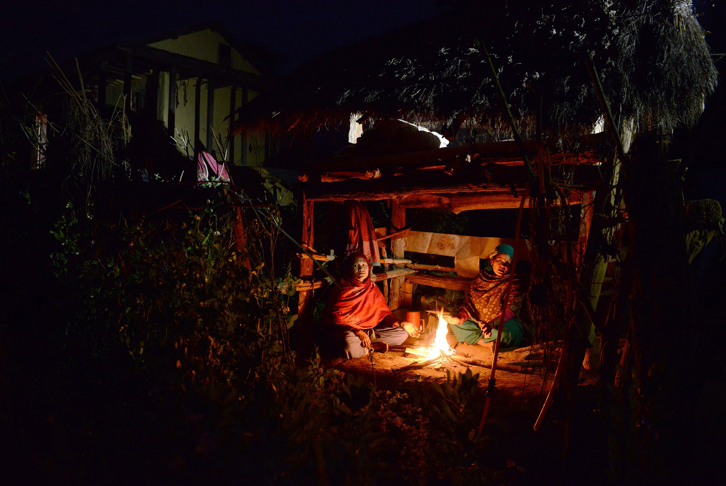 Nepalese women Pabitra Giri (L) and Yum Kumari Giri (R) sit by a fire as they live in a Chhaupadi hut during their menstruation period in Surkhet District, some 520km west of Kathmandu on Feb. 3, 2017.