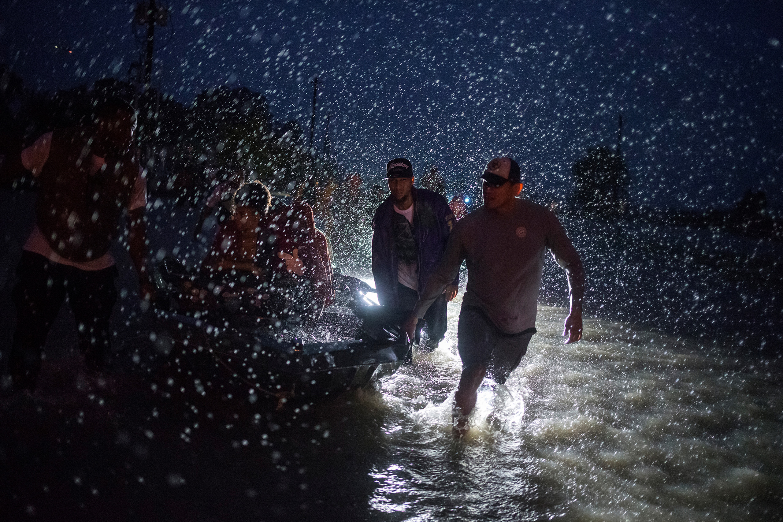 Samaritans help push a boat with evacuees to high ground during a rain storm caused by Tropical Storm Harvey along Tidwell Road in east Houston, on Aug. 28, 2017.