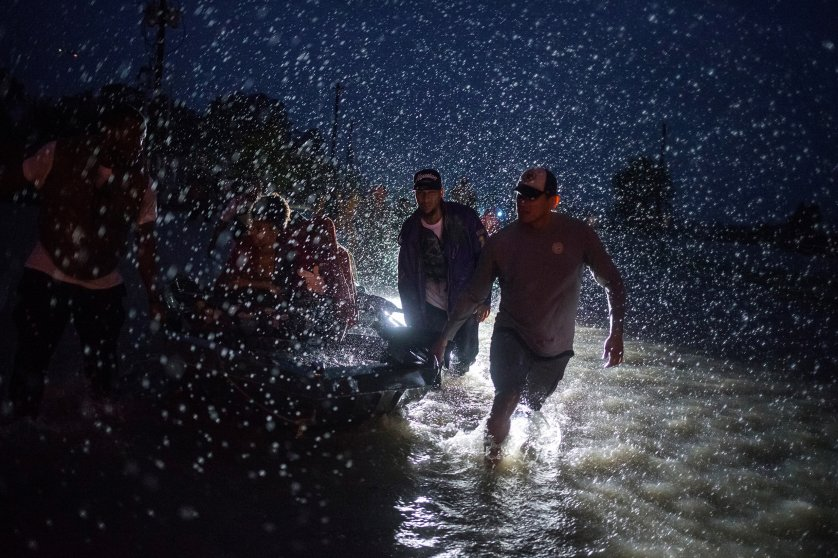 Samaritans help push a boat with evacuees to high ground during a rain storm caused by Tropical Storm Harvey along Tidwell Road in east Houston