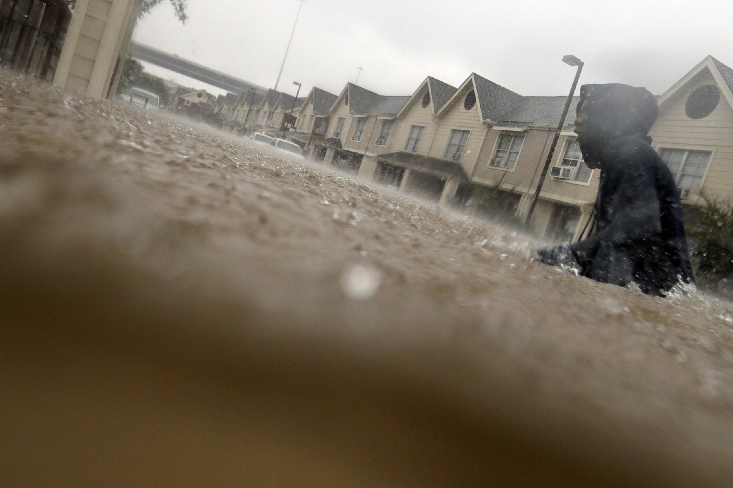 A child makes his way through floodwaters from Tropical Storm Harvey while checking on neighbors at his apartment complex in Houston, Sunday, Aug. 27, 2017. The remnants of Hurricane Harvey sent devastating floods pouring into Houston Sunday as rising water chased thousands of people to rooftops or higher ground. (AP Photo/LM Otero)