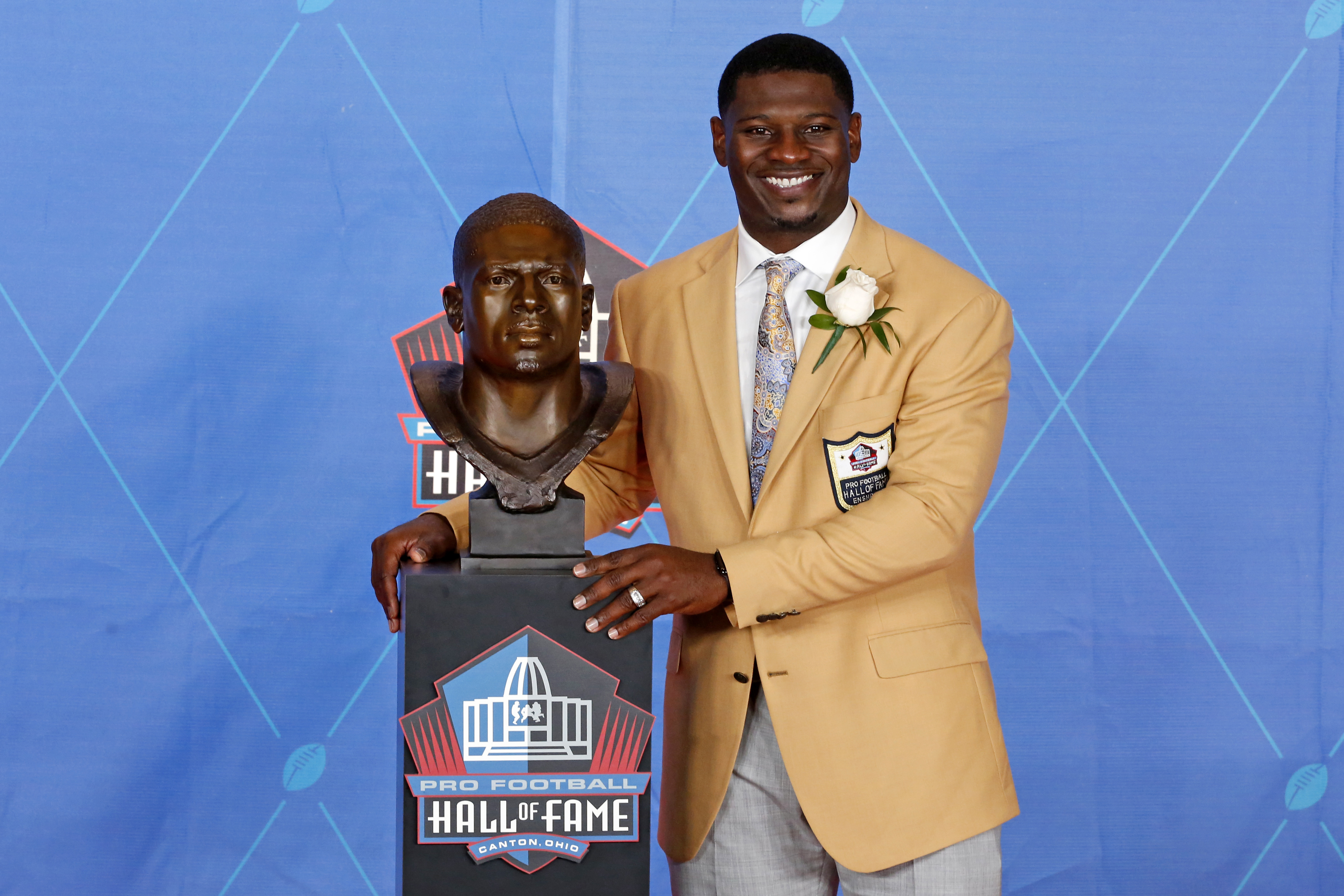 Former NFL player LaDainian Tomlinson poses with a bust of himself during an induction ceremony at the Pro Football Hall of Fame Saturday, Aug. 5, 2017, in Canton, Ohio.