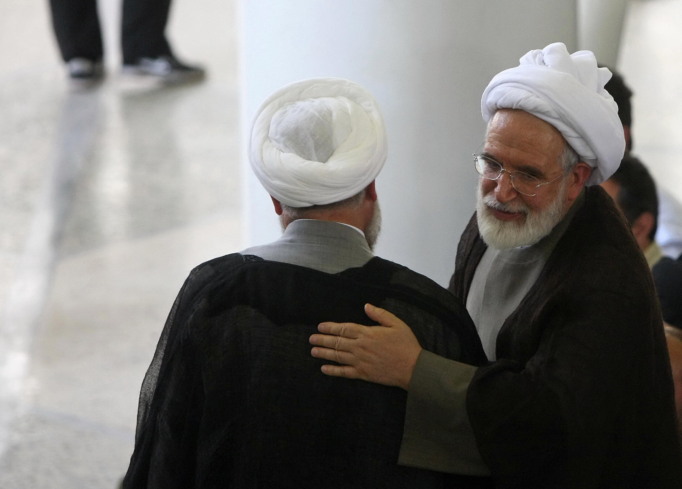 Iranian defeated presidential candidate Mehdi Karroubi (R) speaks with an unidentified cleric following Friday prayers at Tehran University in the Iranian capital on July 17, 2009.