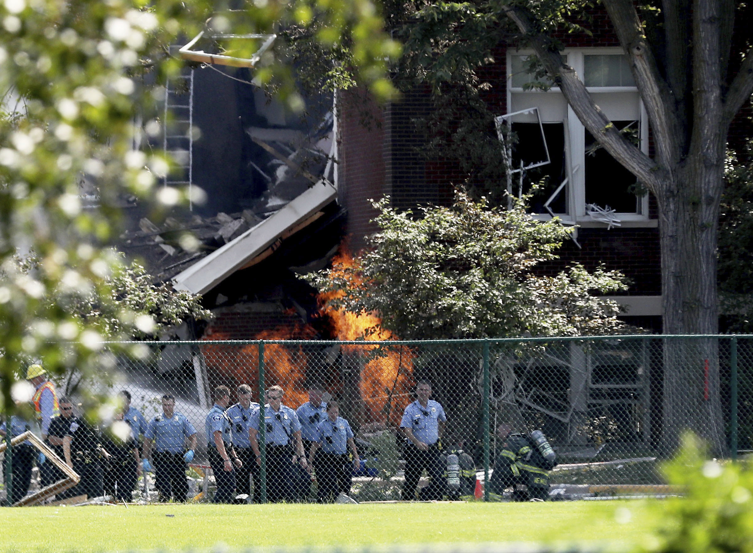 Emergency personnel move away as a gas fire continues to burn following an explosion at Minnehaha Academy on Aug. 2, 2017, in Minneapolis.