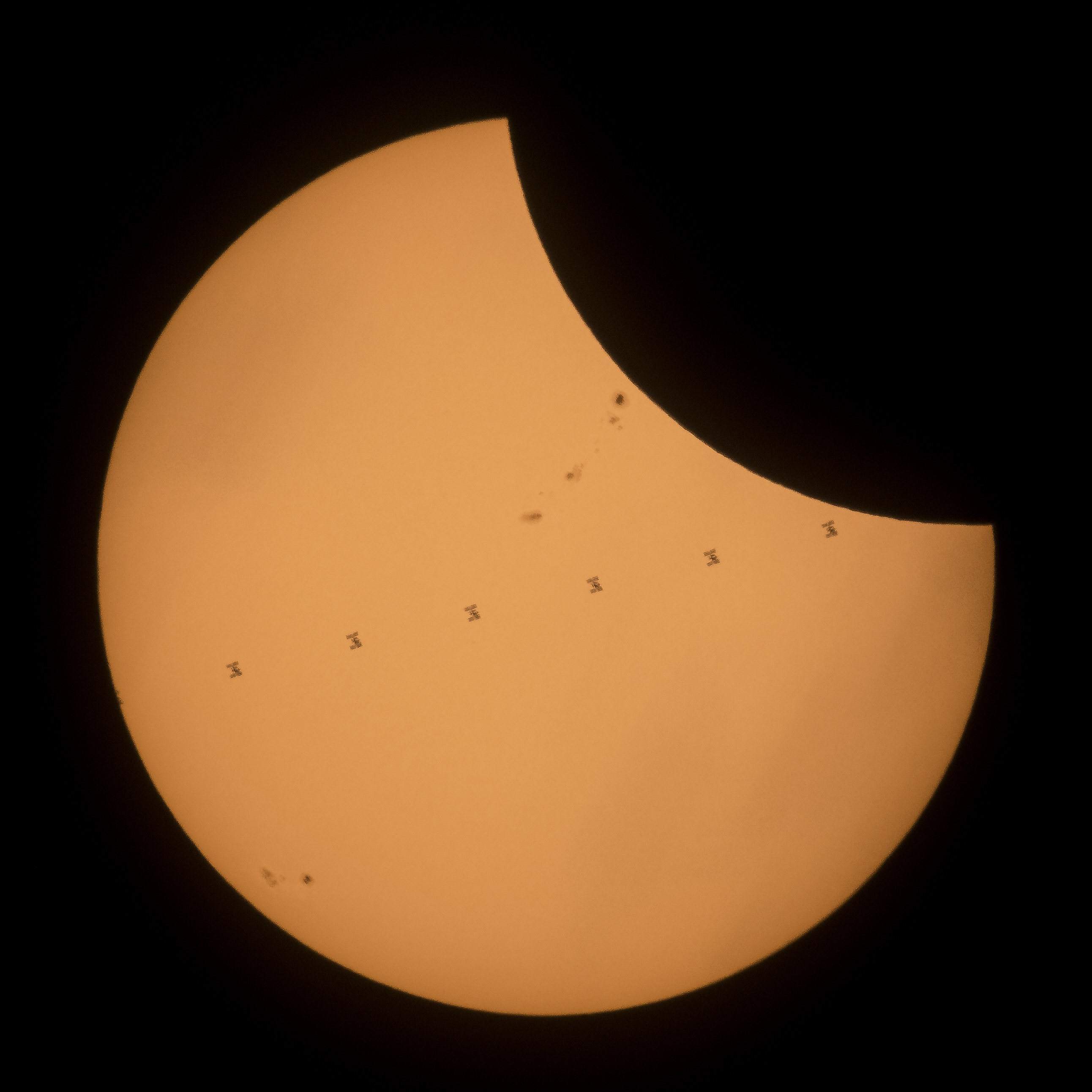 This composite image, made from seven frames, shows the International Space Station, with a crew of six onboard, as it transits the Sun at roughly five miles per second during a partial solar eclipse on Aug. 21, 2017 near Banner, Wyoming.