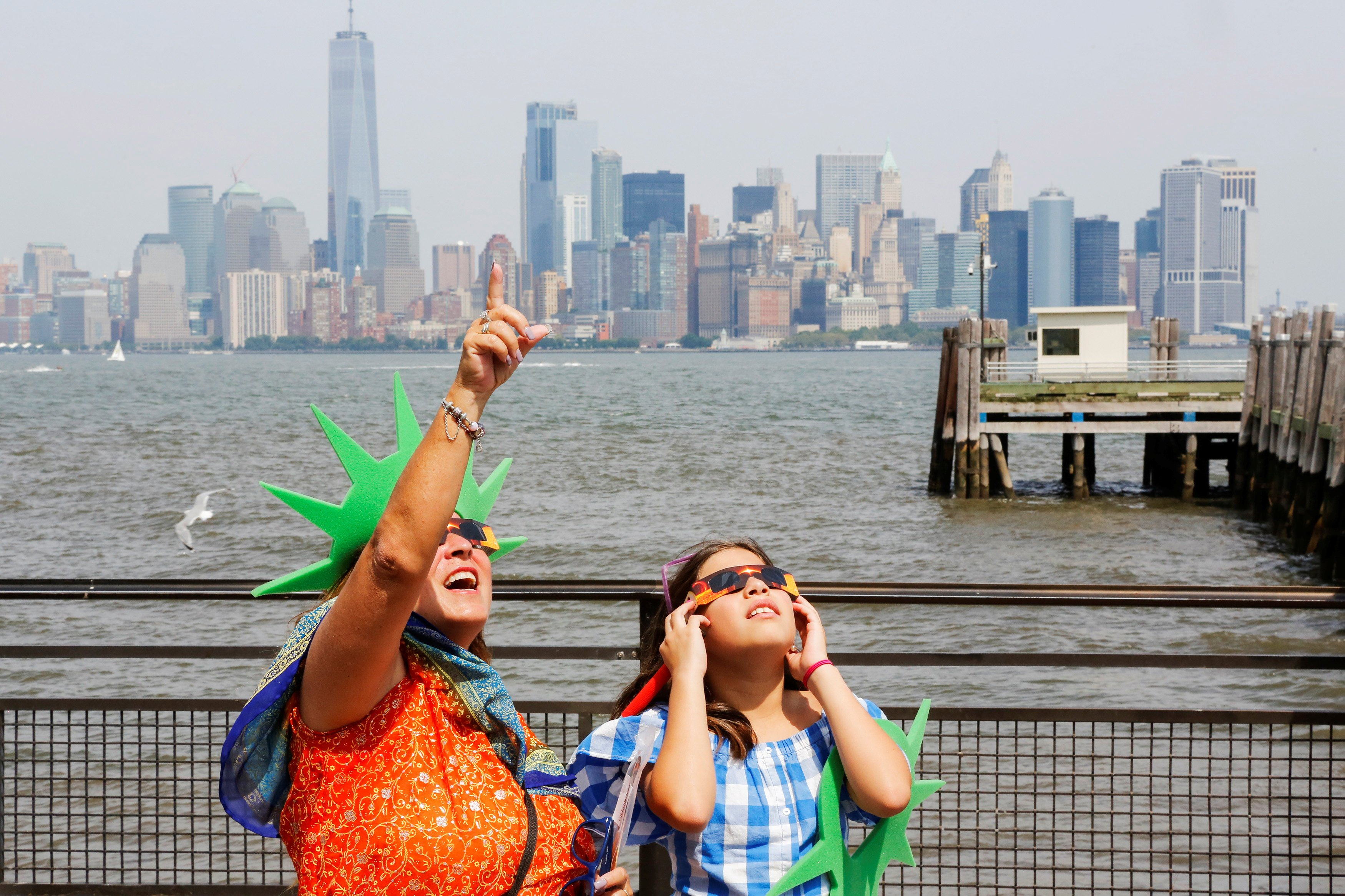 People view the solar eclipse at Liberty State Island as the Lower Manhattan and One World Trade center are seen in the background in New York, on Aug 21, 2017.