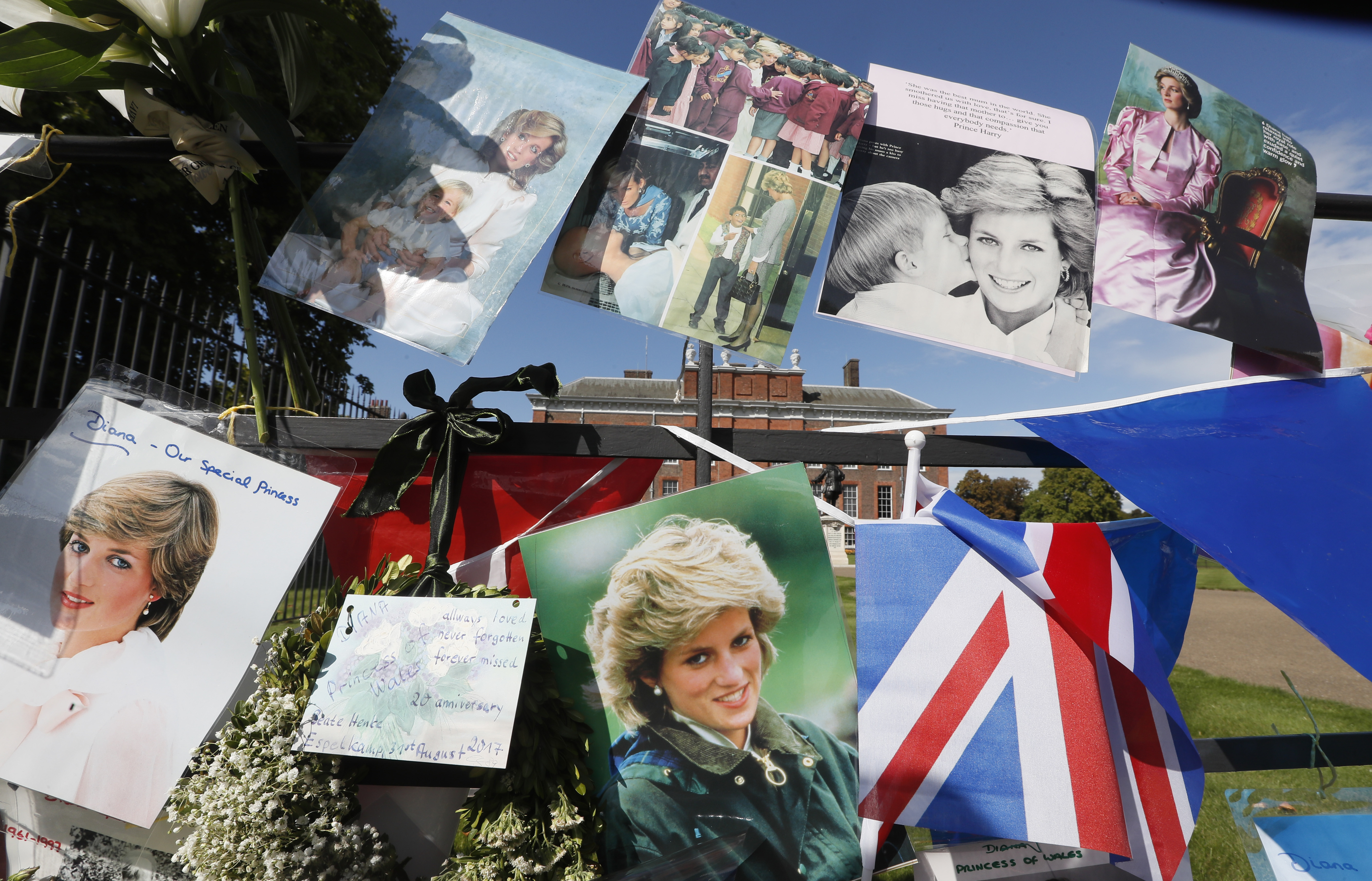 Pictures and flags hang on the gates of Kensington Palace in London to pay tribute to the late Diana, Princess of Wales, Thursday, Aug. 31, 2017. Tributes at the gates are to mark the 20th anniversary of Diana's death, in a car crash in Paris on Aug. 31, 1997.