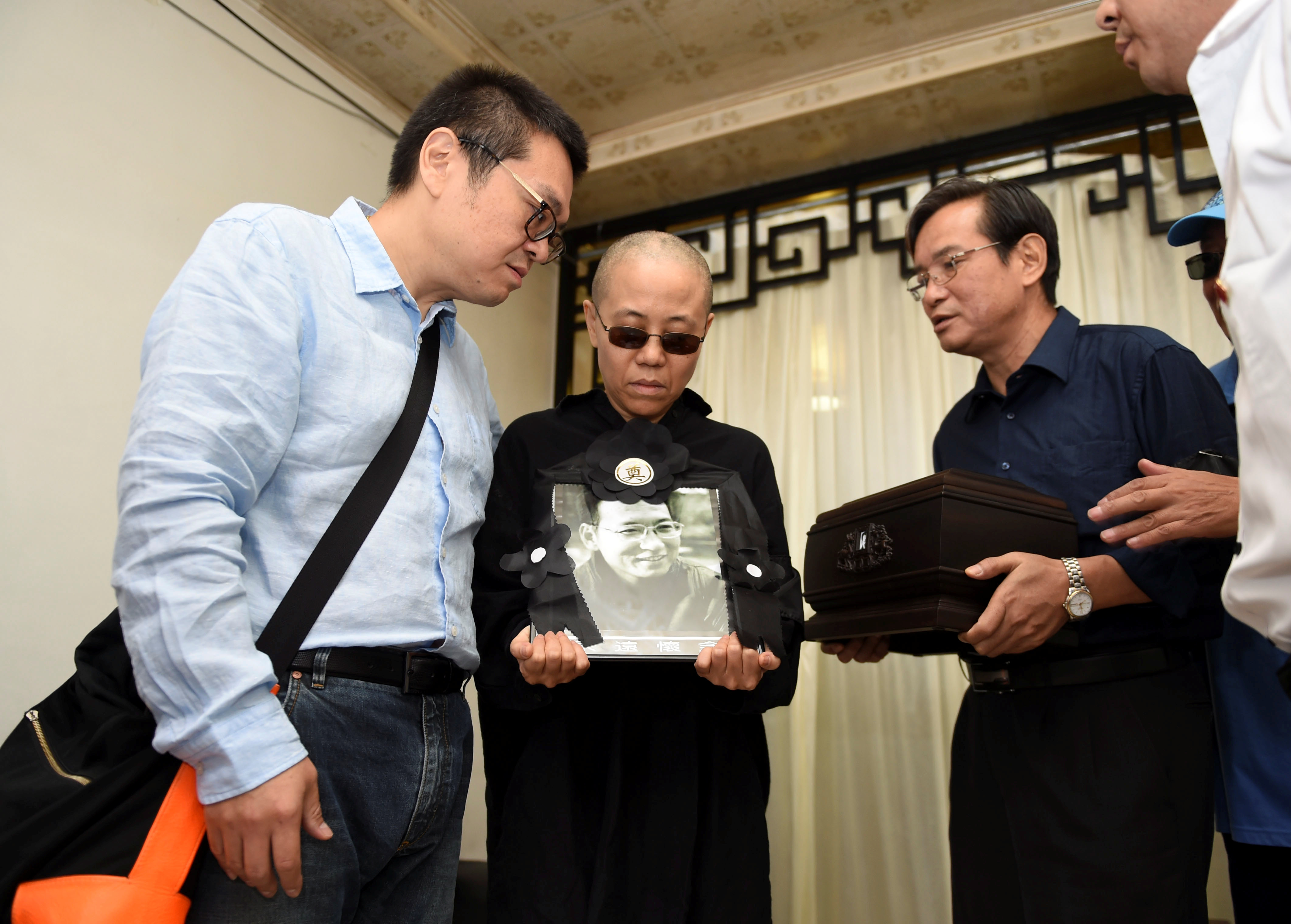 Liu Xia holds a picture of her husband, deceased Chinese Nobel laureate Liu Xiaobo, during his funeral in Shenyang, China on July 15, 2017.