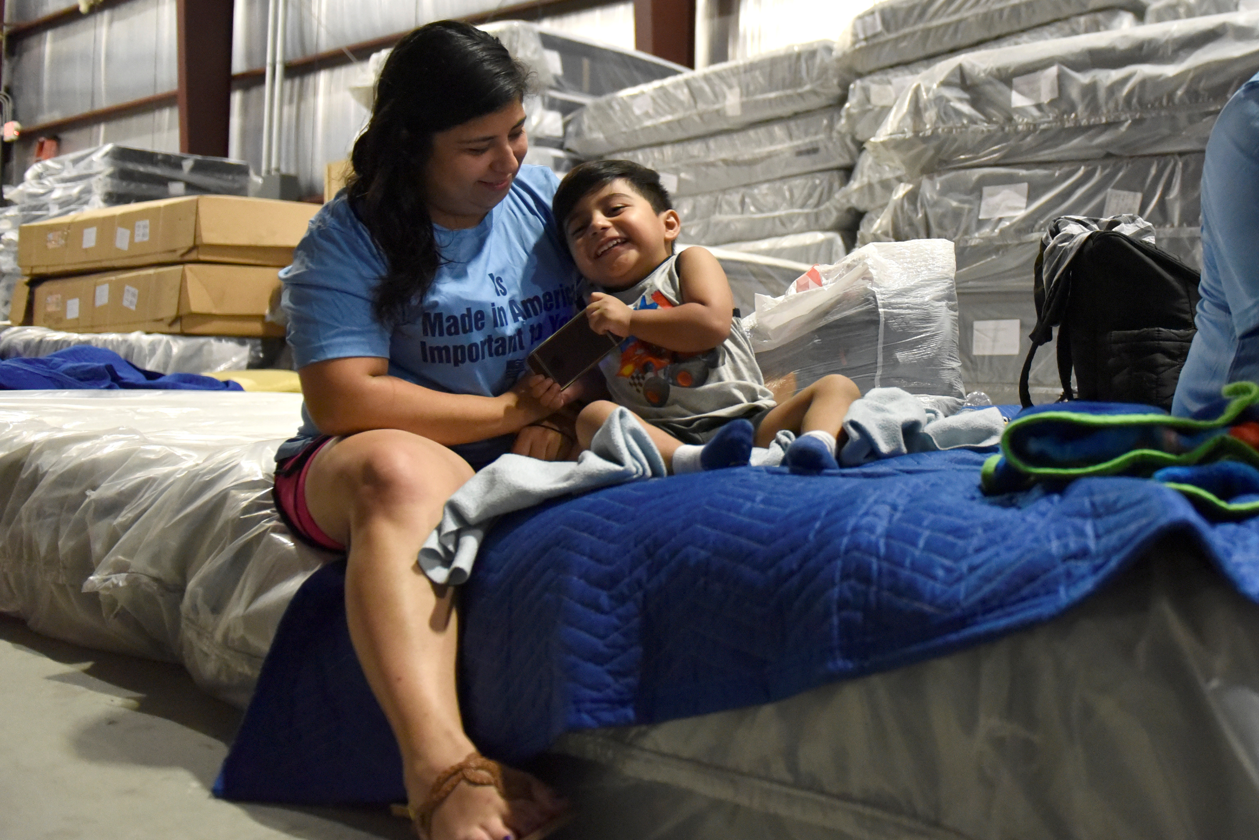 Maria Lopez plays with her son Rafael Lopez, 3, in the warehouse at Gallery Furniture where they have been staying after evacuating their flooded home over the weekend, in Houston, Texas, U.S., August 29, 2017.