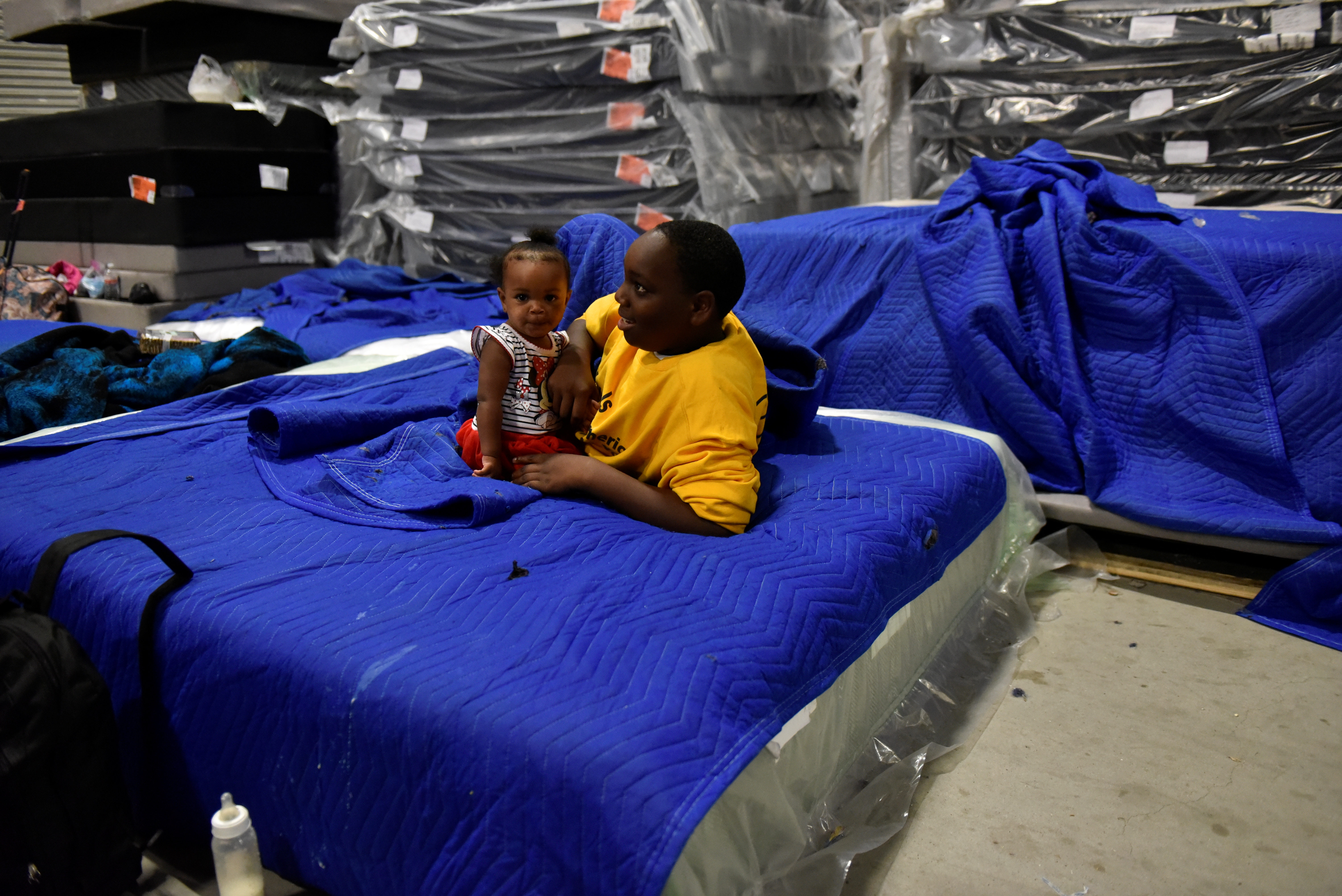 Jakobe Thomas plays with his sister Journey Thomas, 1, in the warehouse at Gallery Furniture where they have been staying after evacuating their flooded home over the weekend, in Houston, Texas, U.S., August 29, 2017. REUTERS/Nick Oxford - RTX3DVUW