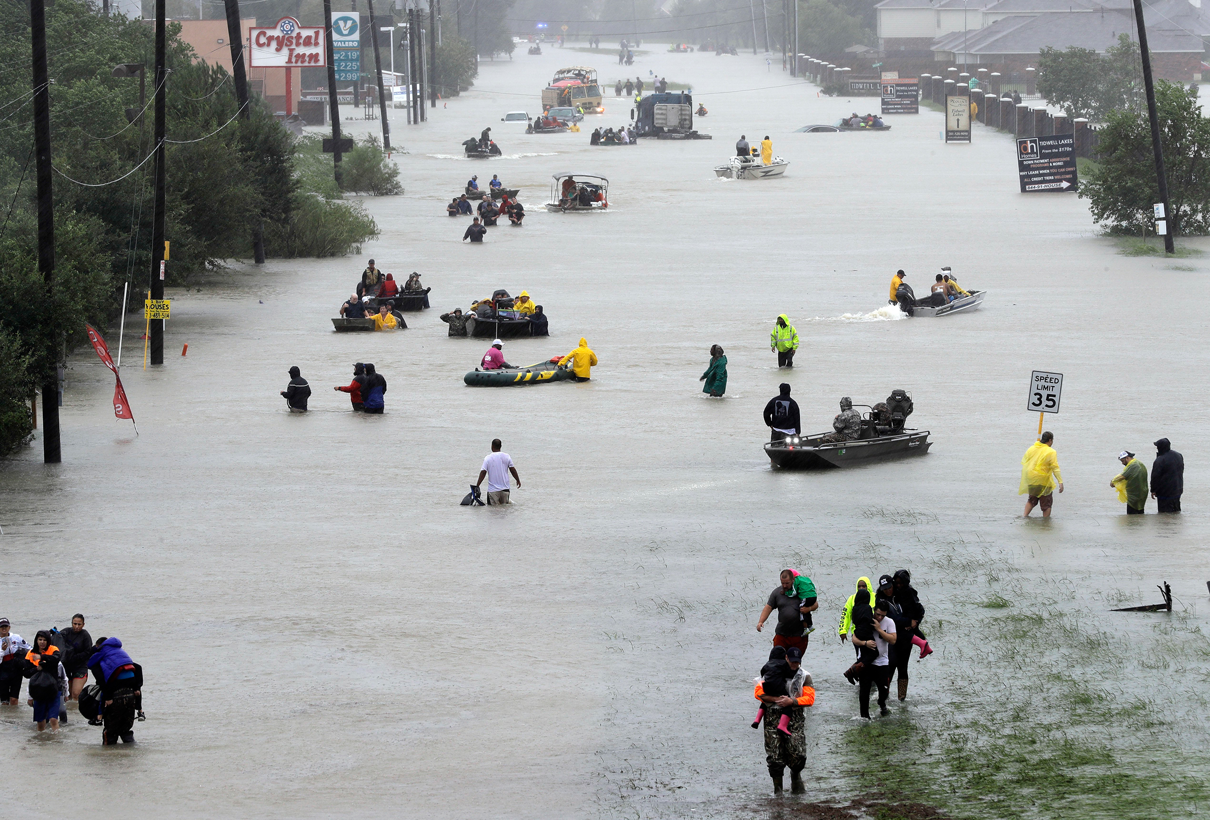 Rescue boats fill a flooded street as flood victims are evacuated floodwaters from Tropical Storm Harvey rise, Aug. 28, 2017, in Houston.