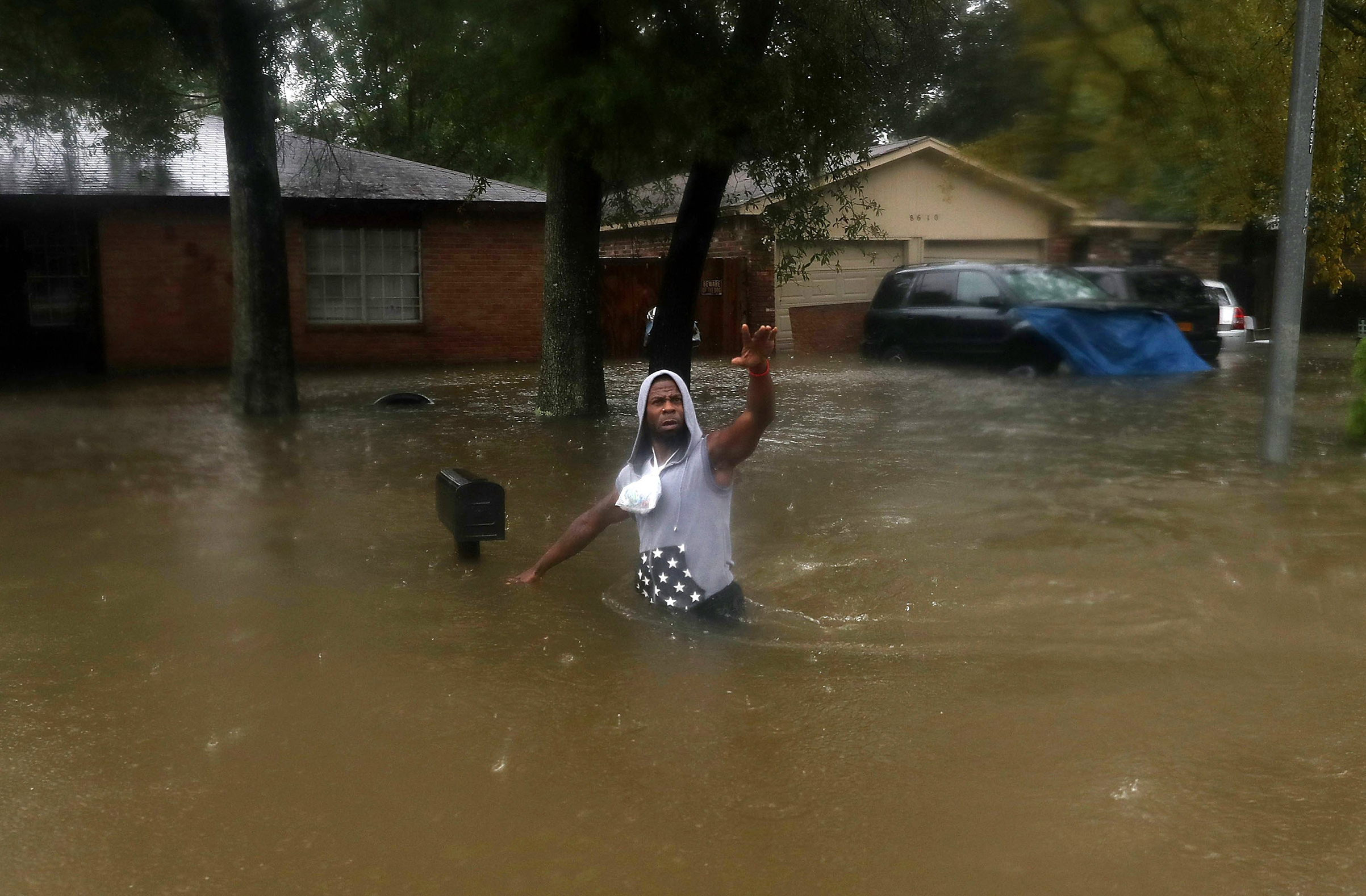 A person waves to rescuers as he walks through a flooded street after the area was inundated with flooding from Hurricane Harvey on Aug. 28, 2017 in Houston.