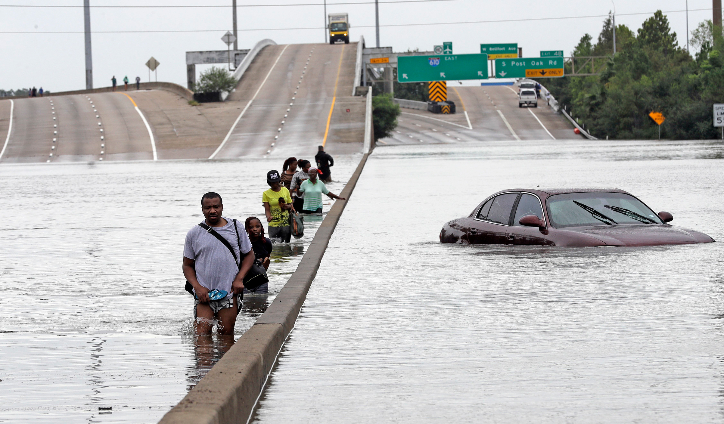Evacuees wade down a flooded section of Interstate 610 as floodwaters from Tropical Storm Harvey rise, Aug. 27, 2017, in Houston.