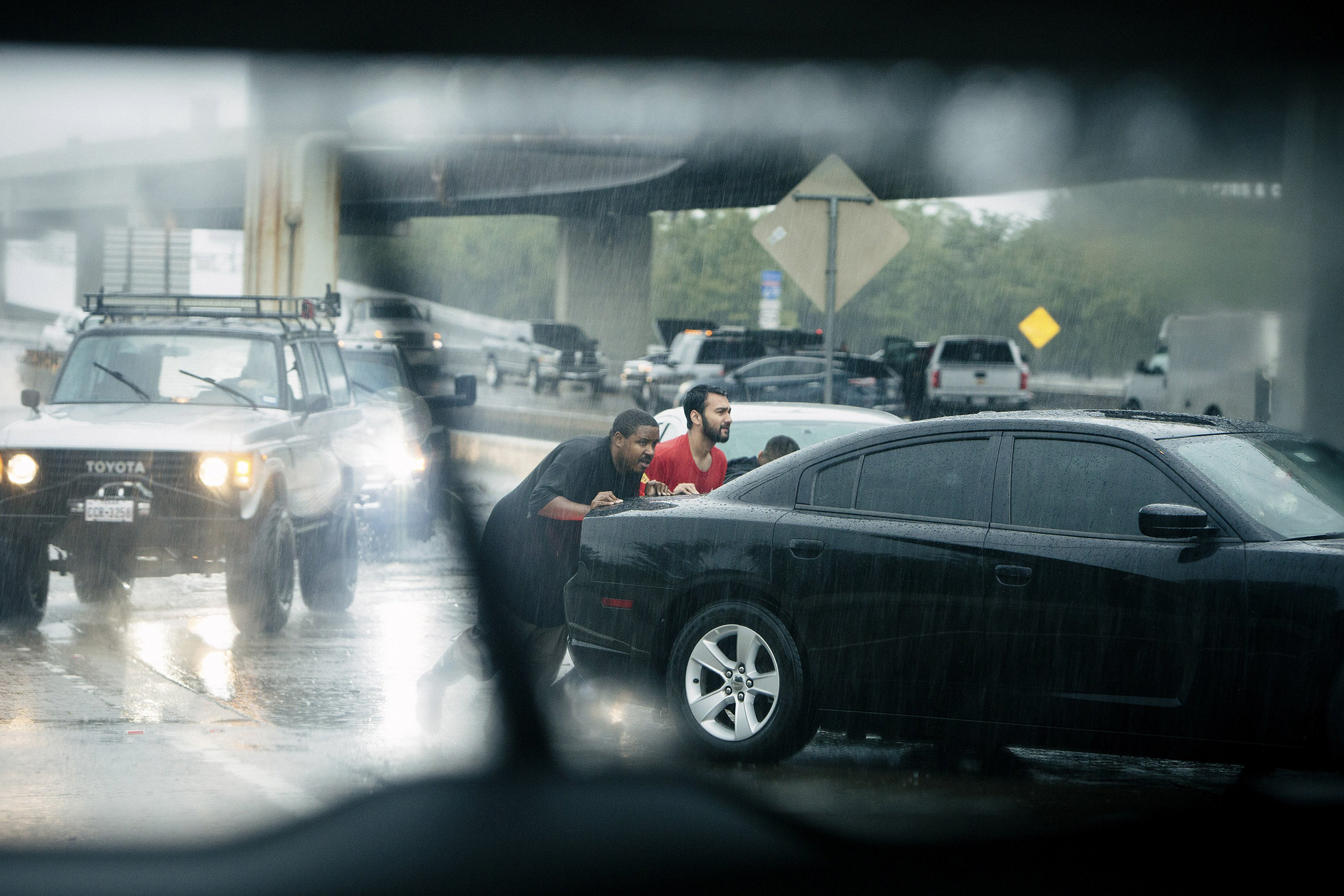 A stalled car gets a push amid heavy rain on a section of Interstate 610 in Houston, Aug. 27, 2017.