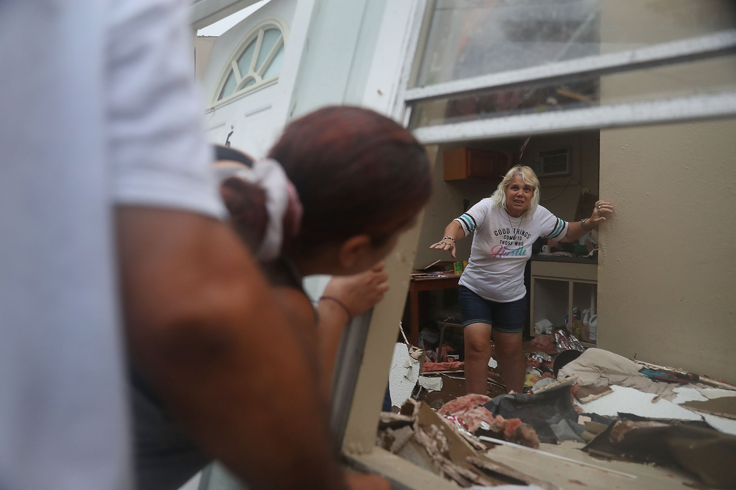 Donna Raney makes her way out of the wreckage of her home as Daisy Graham tells her she will help her out of the window after Hurricane Harvey destroyed the apartment in Rockport, Texas,  on Aug. 26, 2017.
