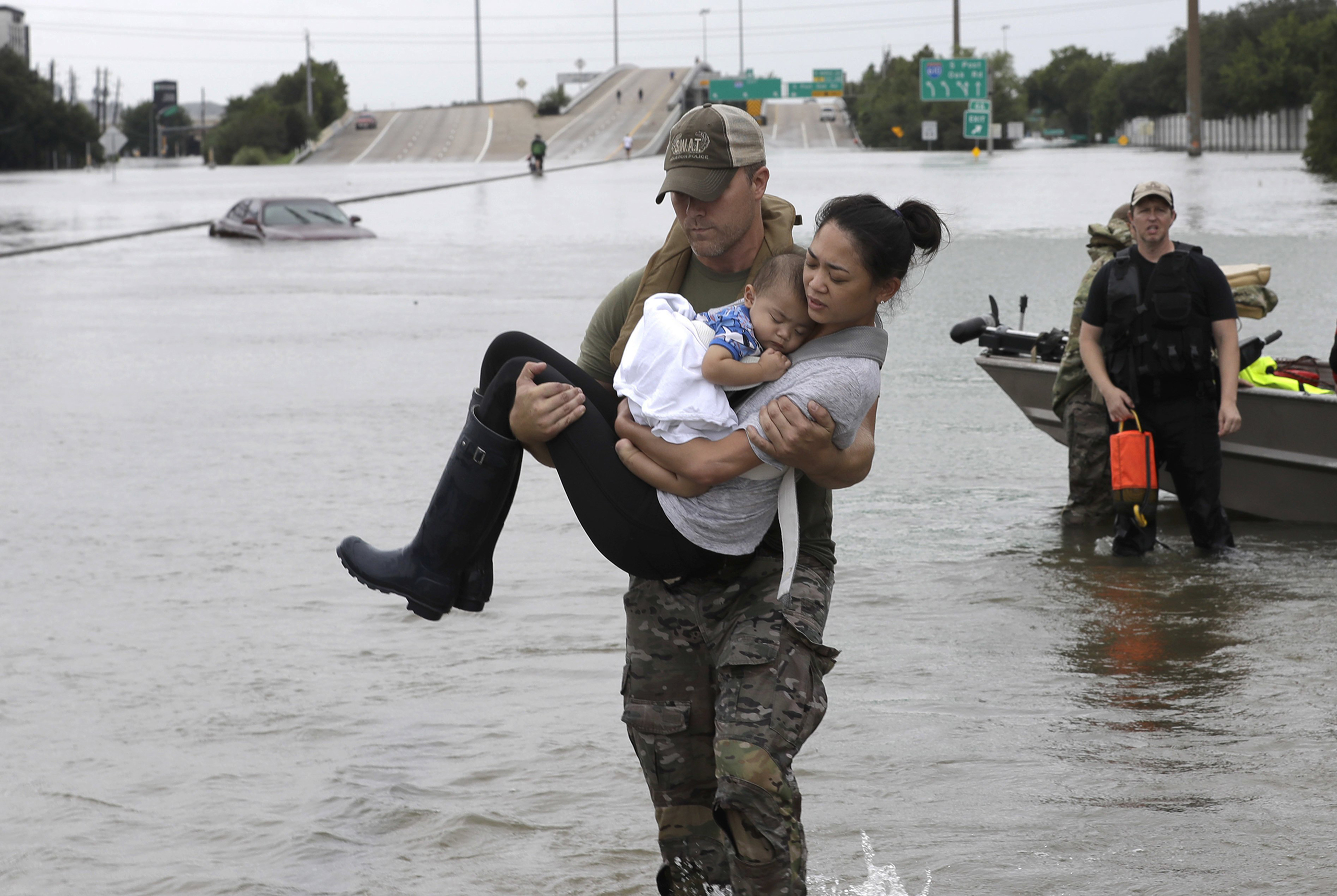 Houston Police SWAT officer Daryl Hudeck carries Catherine Pham and her 13-month-old son Aiden after rescuing them from their home surrounded by floodwaters from Tropical Storm Harvey in Houston, on Aug. 27, 2017.