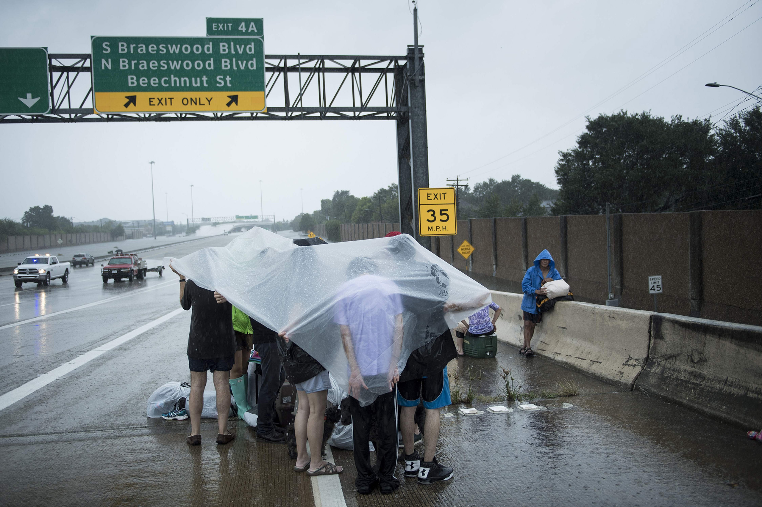 Evacuation residents from the Meyerland wait on an I-610 overpass for further help during the aftermath of Hurricane Harvey Aug. 27, 2017 in Houston.
