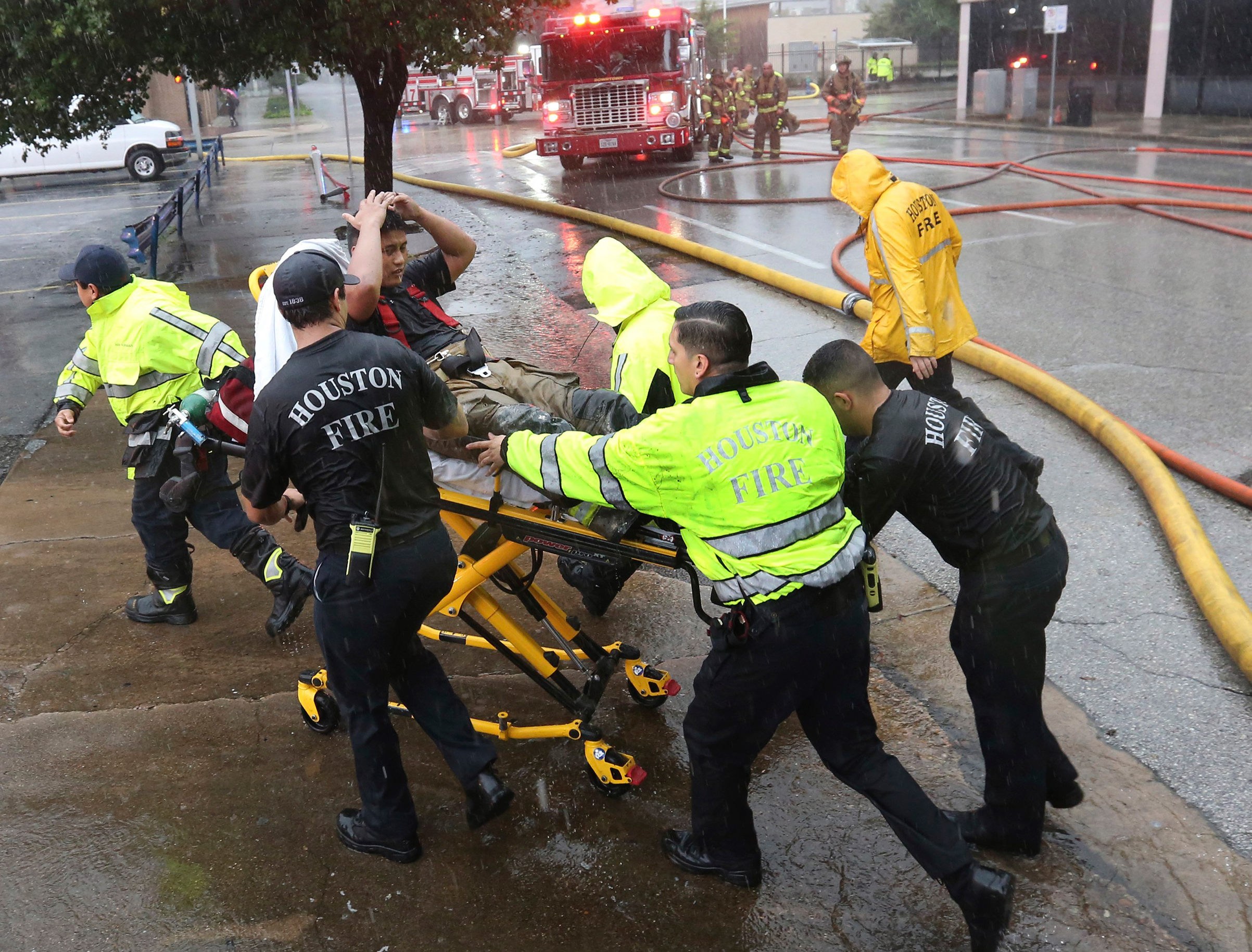 Rain from Tropical Storm Harvey falls as a firefighter is wheeled to a waiting ambulance after he became fatigued while fighting an office building fire in downtown in Houston, Aug. 28, 2017.