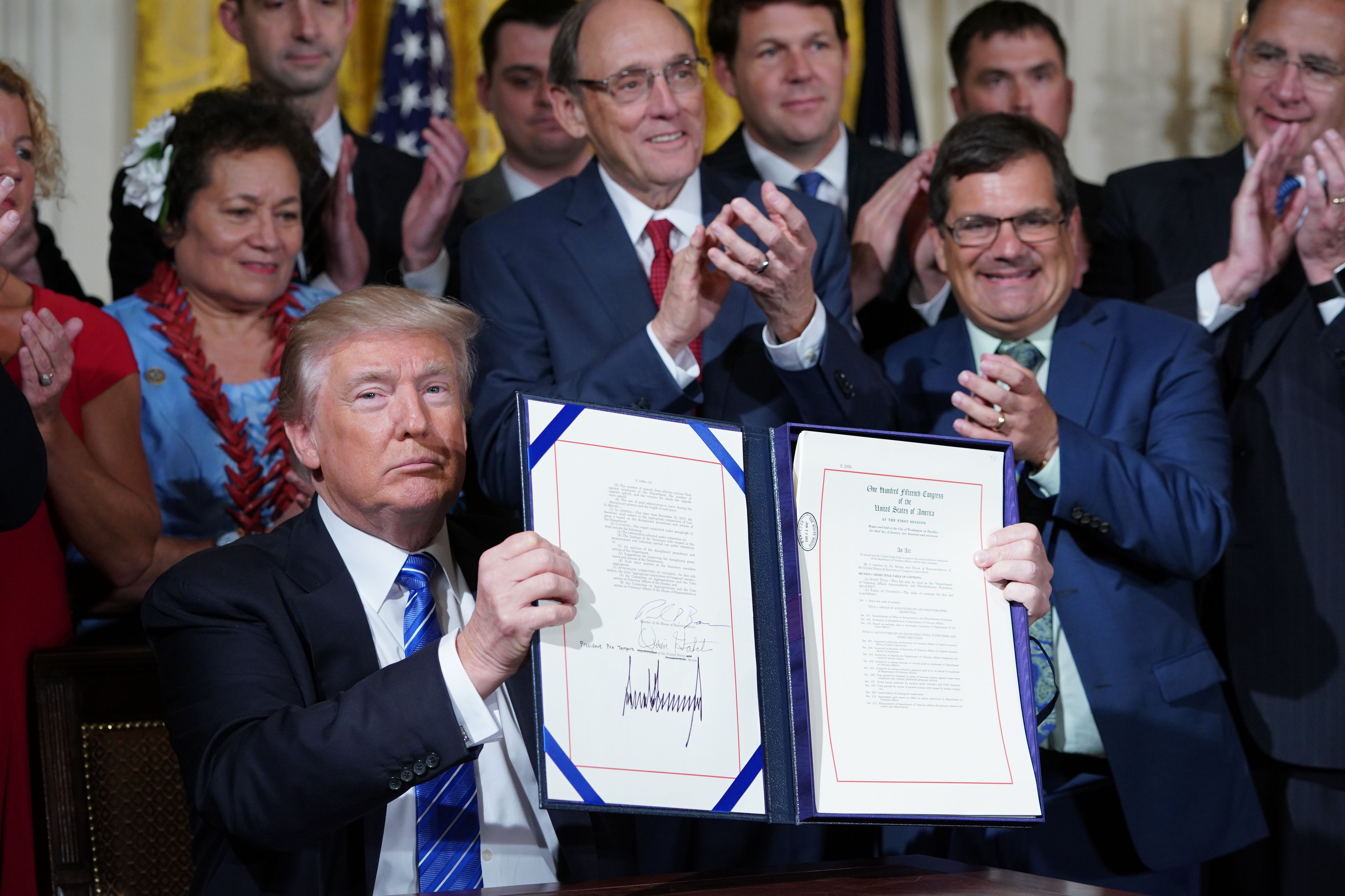 US President Donald Trump holds up the bill after signing the Department of Veterans Affairs Accountability and Whistleblower Protection Act of 2017, on June 23, 2017, in the East Room of the White House in Washington, DC.